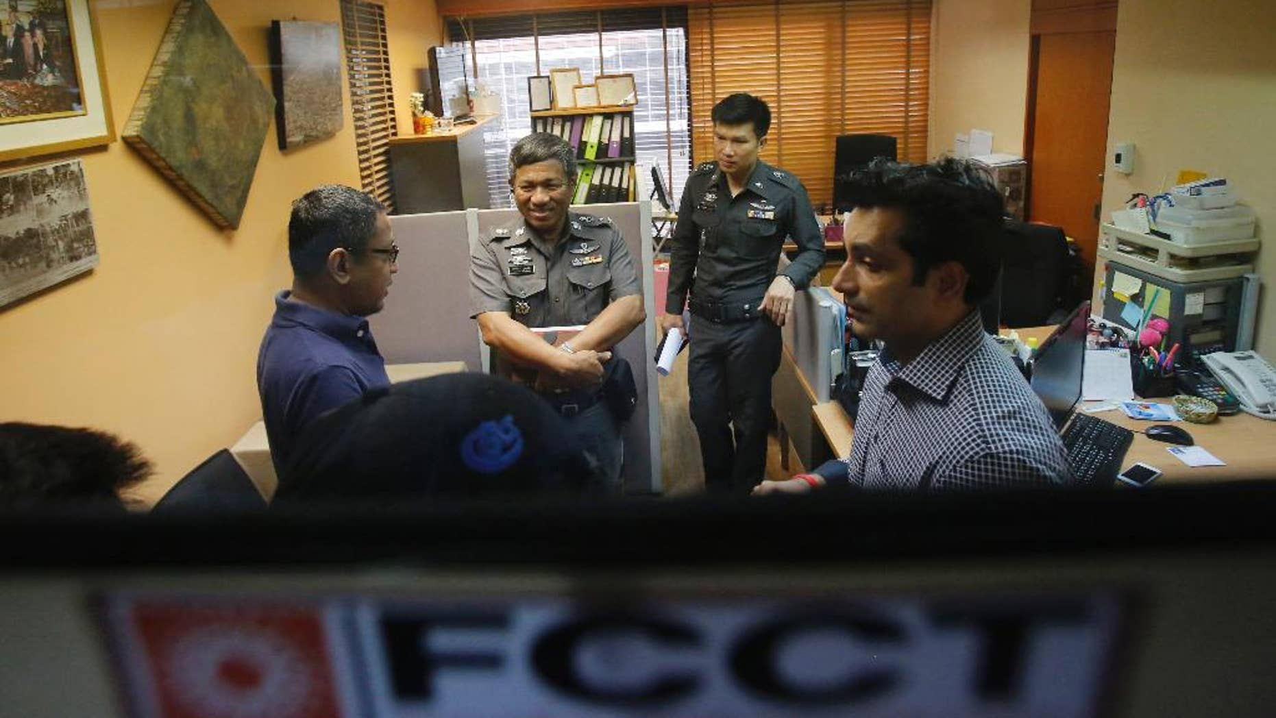 """Sunai Phasuk, left, Human Rights Watch's senior researcher in Asia, and Umesh Pandey, a board member of Foreign Correspondents of Thailand, right, talk to policemen at the Foreign Correspondents Club of Thailand in Bangkok, Thailand Friday, June 26, 2015. Thai authorities on Friday forced the human rights group to cancel the launch of its report on the Vietnamese government's persecution of an ethnic minority, citing it could affect national security and bilateral relations. Thai police said in a statement Friday the scheduled event at the club could """"have an impact on the country's security or could affect the friendship and cooperation between Thailand and Vietnam."""" (AP Photo/Sakchai Lalit)"""