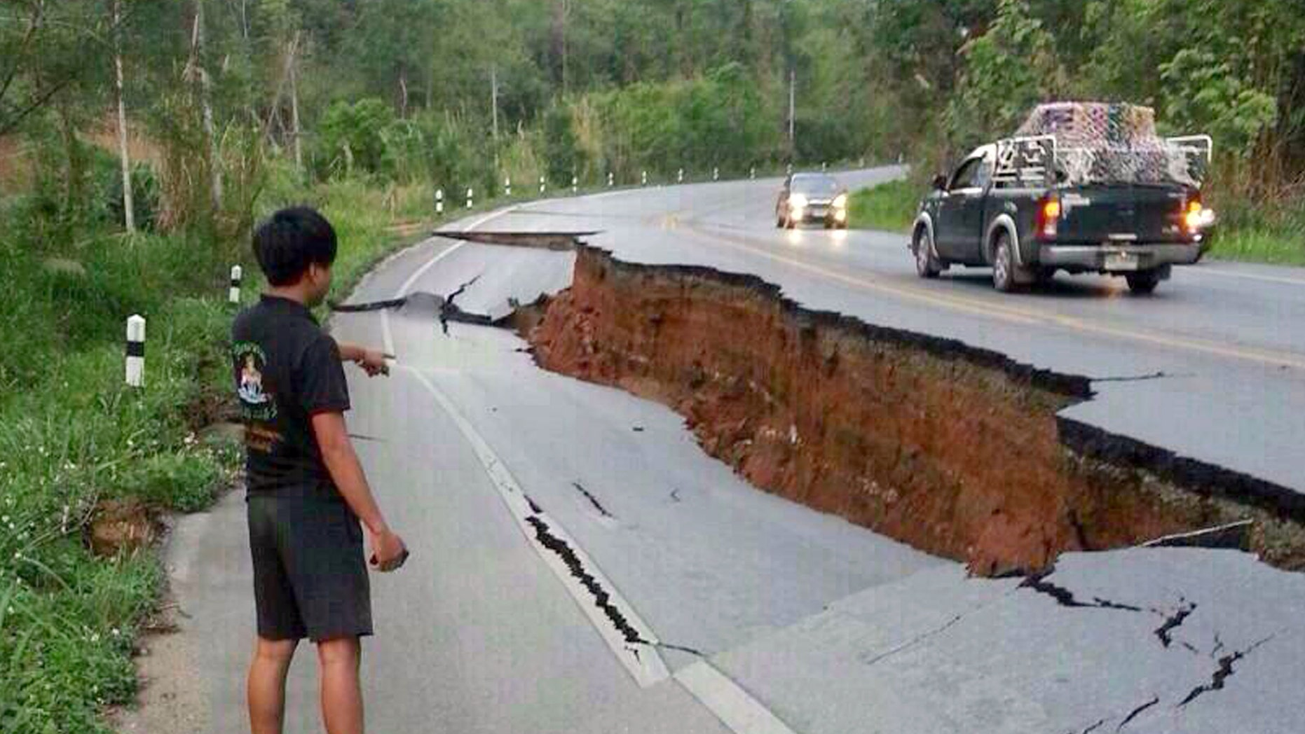 May 5, 2014 - A man eyes a big crack on a damaged road following a strong earthquake in Phan district of Chiang Rai province, northern Thailand. The strong quake shook northern Thailand and Myanmar Monday evening, and light damage was reported.