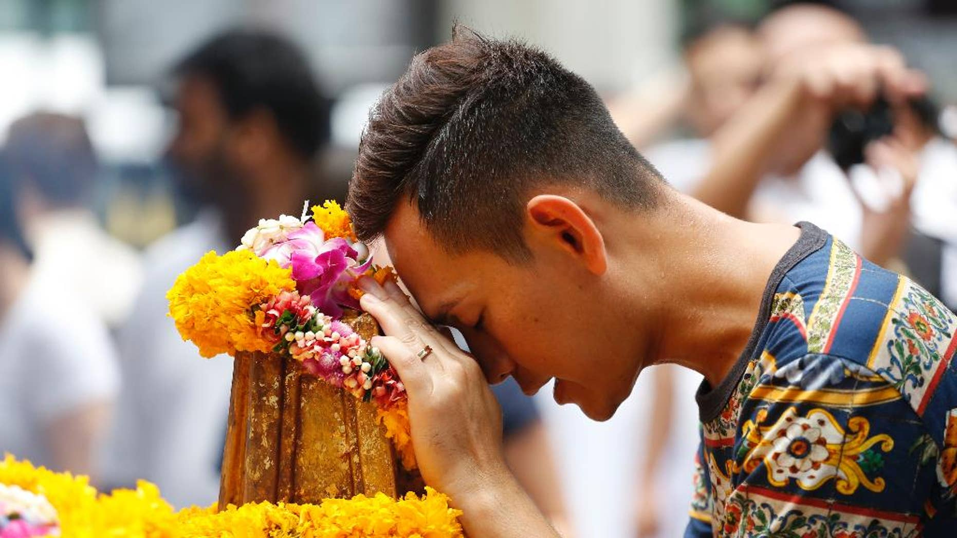 In this Aug. 24, 2015, file photo, a man prays at the Erawan Shrine at Rajprasong intersection, the scene of the Aug. 17 bombing, in Bangkok, Thailand. Thai police probing Bangkok's deadly bombing said on Monday, Aug. 31, 2015, that they have discovered bomb-making materials during a raid of a second apartment on the outskirts of the capital. (AP Photo/Sakchai Lalit, File)