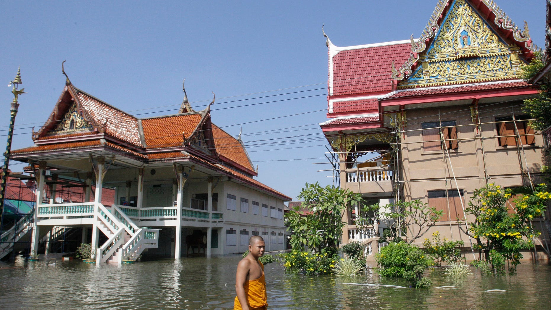 Oct. 19, 2011: Thai Buddhist monk wades through a flooded street at Ban Kadee temple in Phatum Thani province, north of Bangkok ,Thailand.