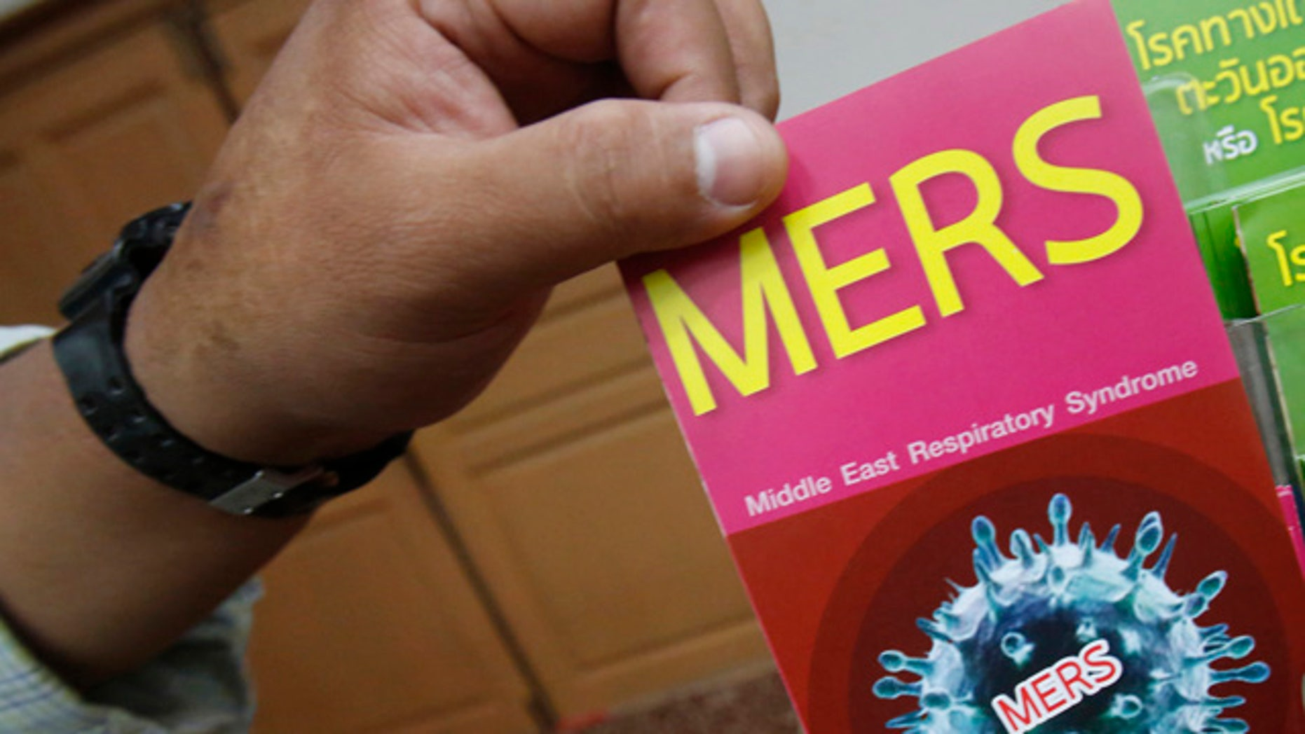 June 18, 2015: A Thai officer takes a flyer after Public Health Minister Rajata Rajatanavin's press conference in Bangkok. Thailand says it has confirmed its first known case of the deadly MERS virus, a man who arrived from a Middle Eastern country for treatment of a heart condition. (AP Photo/Sakchai Lalit)