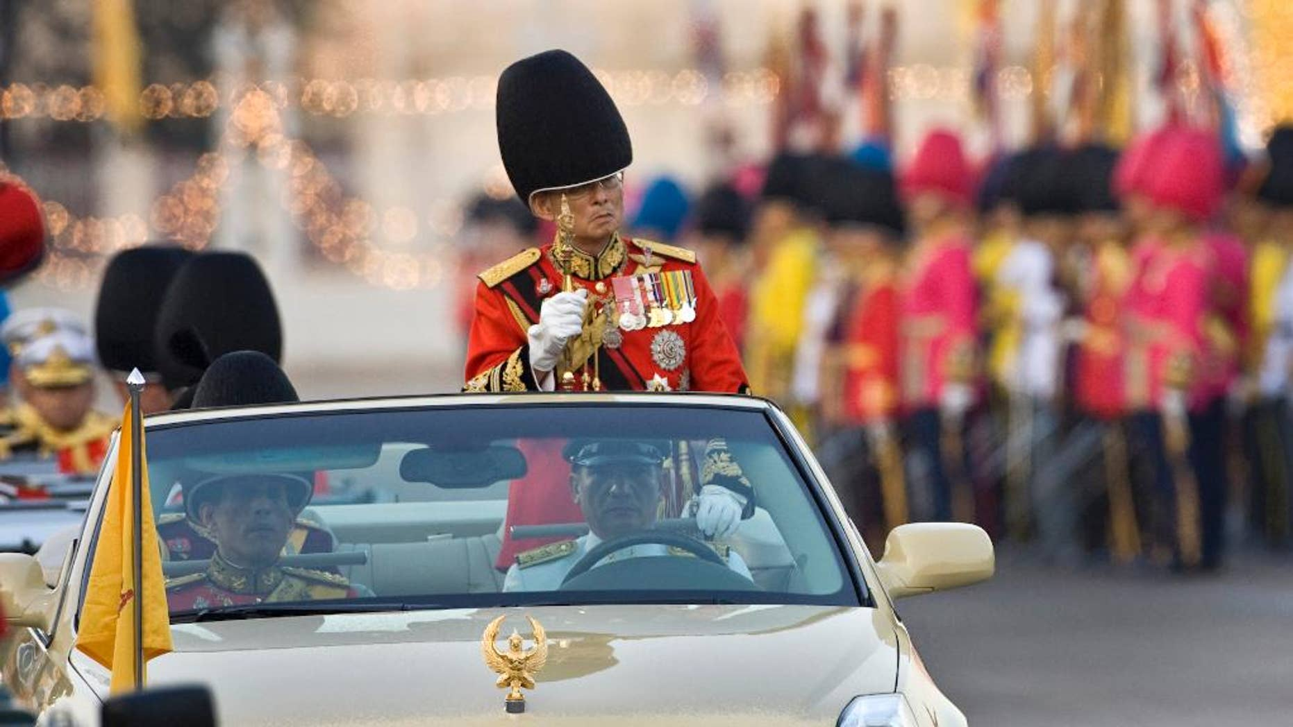 FILE - In this Dec. 2, 2008 file photo, Thailand's King Bhumibol Adulyadej reviews the honor guard in Bangkok, Thailand. Prosecutors in Thailand have charged two people with defaming the country's monarchy in a stage performance at a university last year, moving on a complaint filed by a group of royalists, a lawyer said Tuesday, Oct. 28, 2014. (AP Photo/David Longstreath, File)