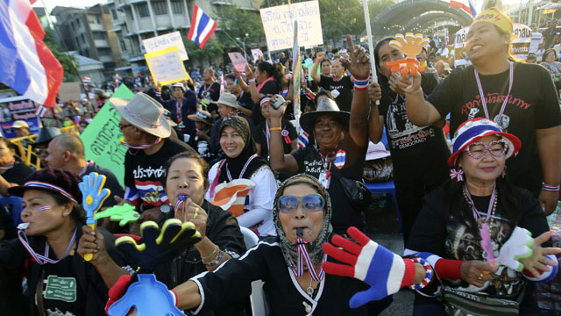 December 1, 2013: Anti-government protesters wave Thai national flags and clapping tools during rally at the Democracy Monument in Bangkok, Thailand. Aggressive political protests in the Thai capital turned violent late Saturday with at least one man killed and several wounded by gunshots in street fighting between supporters and opponents of Prime Minister Yingluck Shinawatra.(AP Photo)