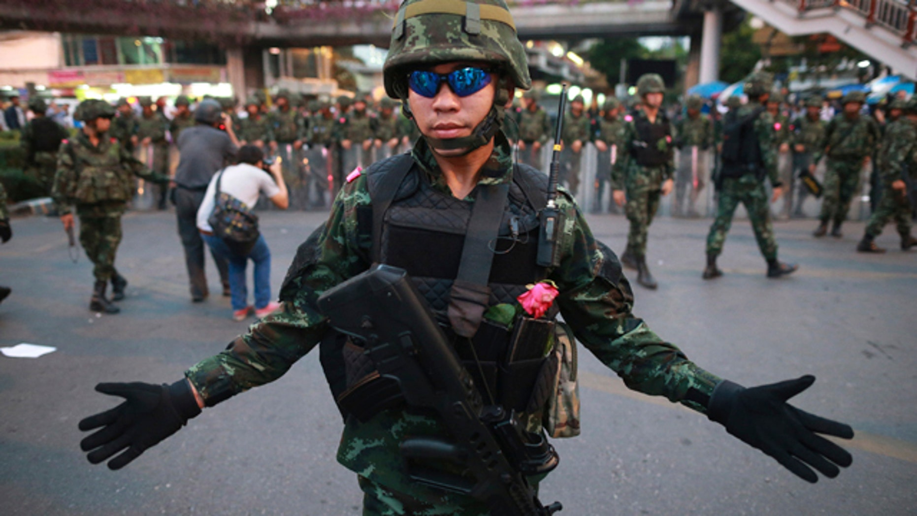 May 26, 2014: A Thai soldier gestures as he and his colleagues guard the Victory Monument during an anti-coup demonstration in Bangkok.(AP Photo/Wason Wanichakorn)