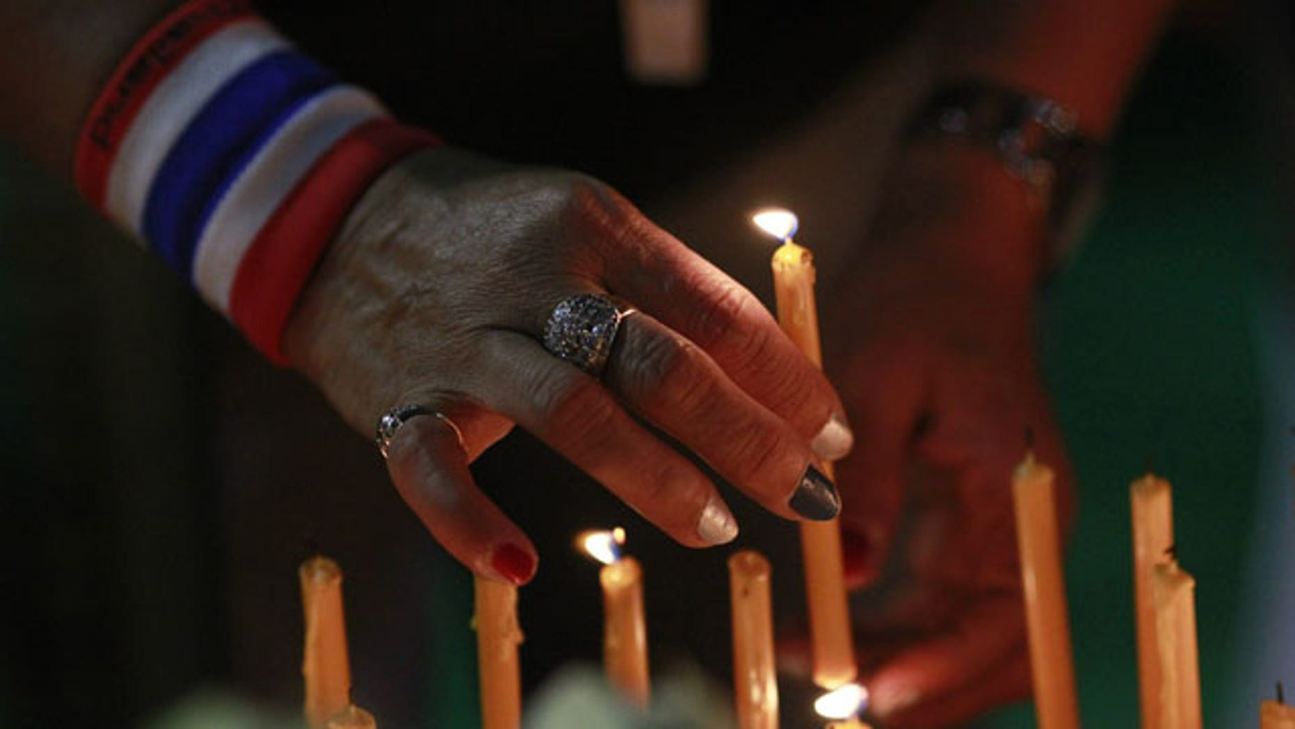 January 18, 2014: An anti-government protester lights a candle during a condolence ceremony for protester Prakong Chujan, who died in Friday's grenade attack at Lumpini rally site in Bangkok, Thailand. (AP)