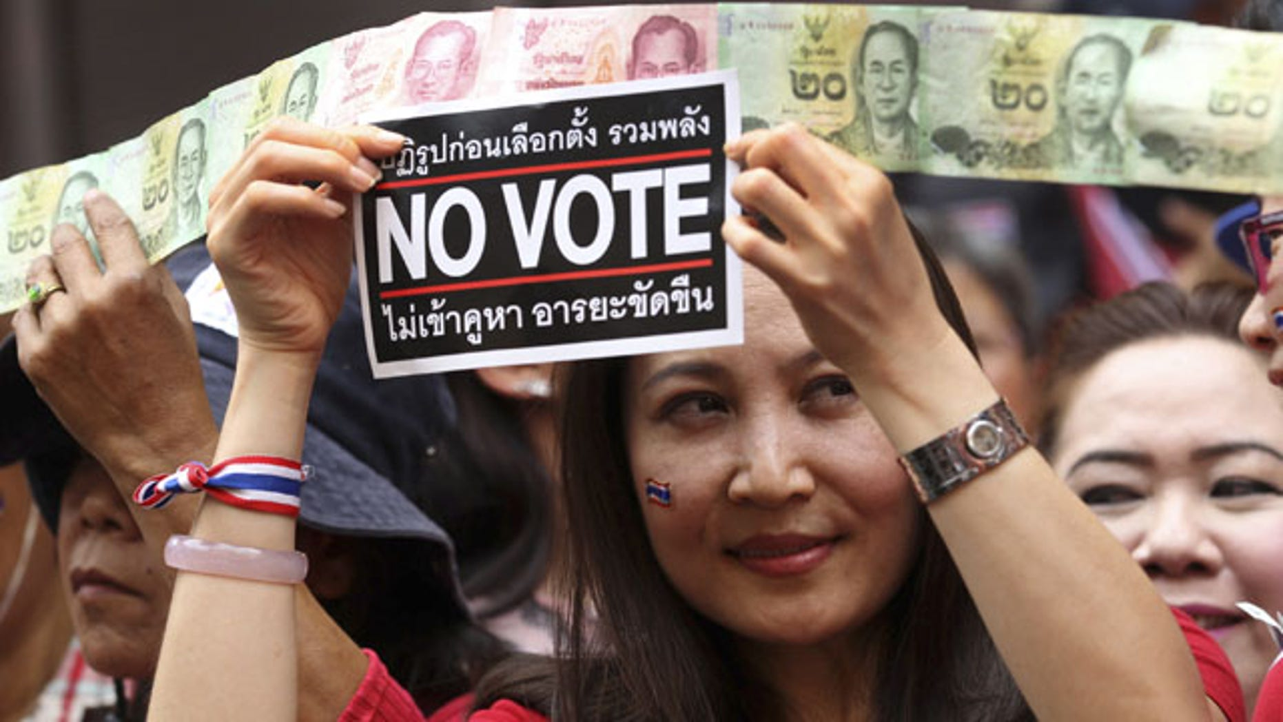 "February 1, 2014: Anti-government supporters display a ""No vote"" sticker and donation for the cause during a march through China Town in Bangkok, Thailand. (AP)"