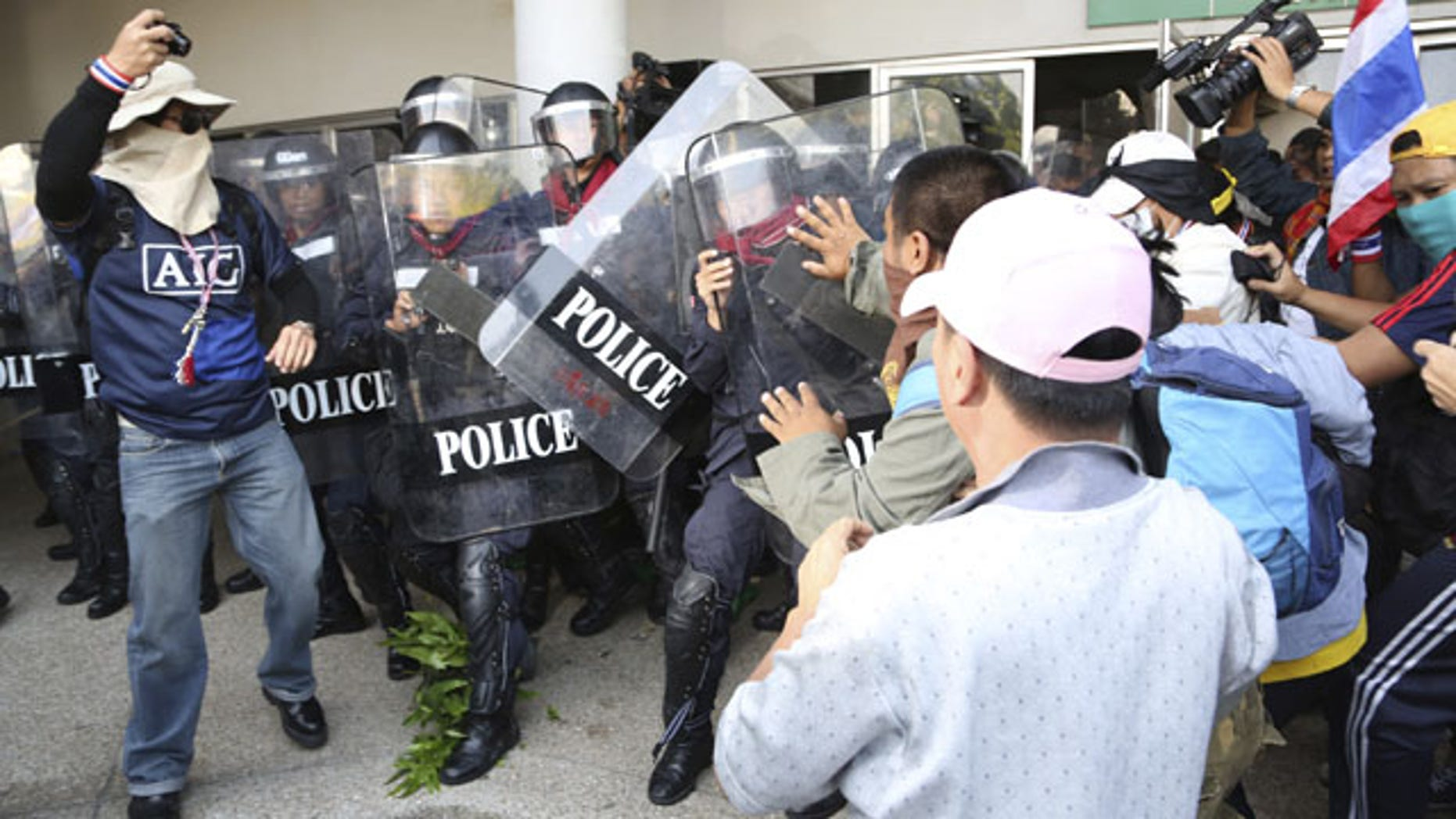 December 25, 2013: Thai anti-government protesters scuffle with riot policemen in an attempt to disrupt the election registration at a sport gymnasium in Bangkok. Thai Prime Minister Yingluck Shinawatra on Wednesday proposed the formation of a national reform council tasked with finding solutions to the political turmoil that is splitting the country and paralyzing governance. (AP Photo/Apichart Weerawong)