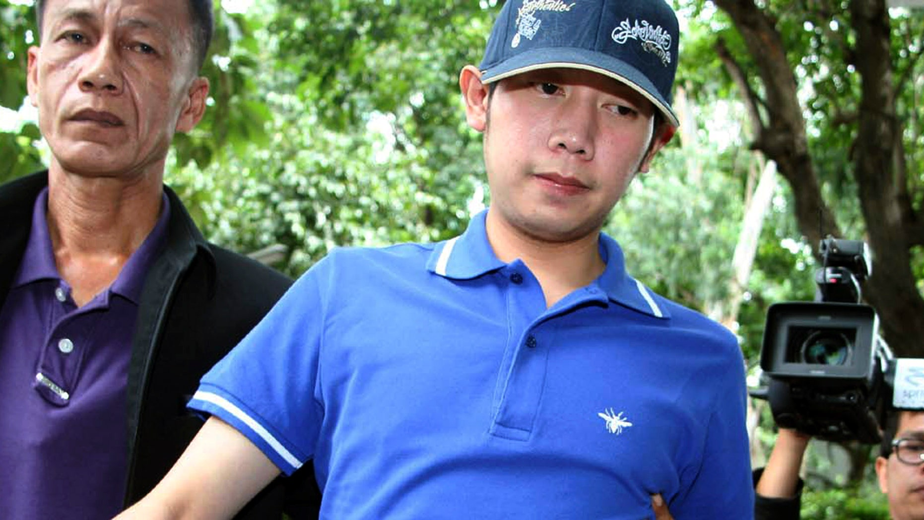 Sept. 3, 2012: Vorayuth Yoovidhya, a grandson of late Red Bull founder Chaleo Yoovidhaya, is taken by a plain-clothes police officer for investigation in Bangkok, Thailand.