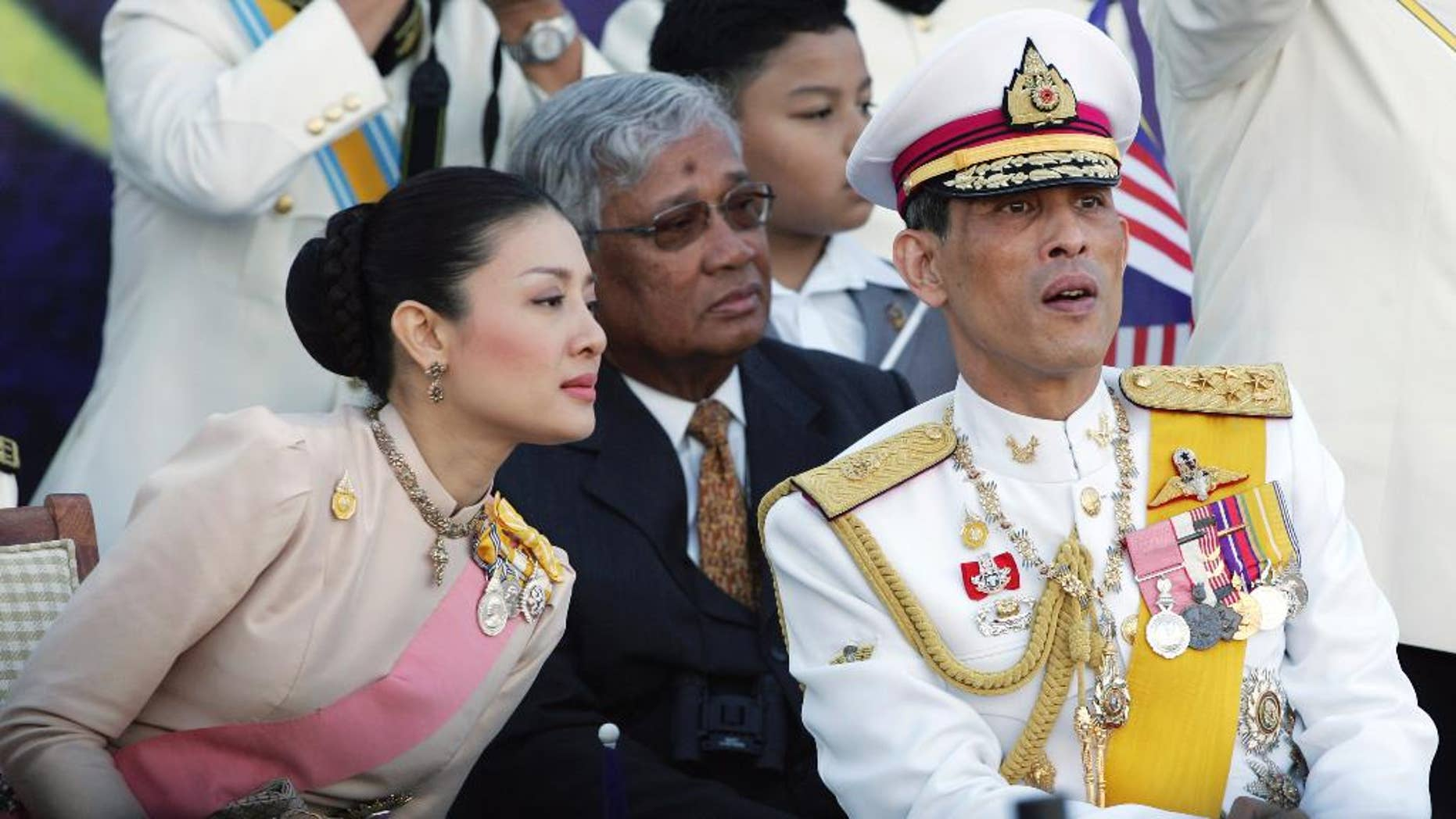 """FILE - In this Aug. 31, 2007 file photo, Thailand's Crown Prince Vajiralongkorn, right, chats with his royal consort Princess Srirasm as they watch a parade at the historic Merdeka square in downtown Kuala Lumpur,  Malaysia. Thailand's Crown Prince Vajiralongkorn has asked the government to strip his wife's family of their royally issued surname, the latest development in a high-profile crackdown that involves senior members of the police force. The move came after at least three of Princess Srirasm's relatives were arrested as part of the probe. In a letter dated Friday, Nov. 28, 2014 but released over the weekend, the crown prince ordered the """"cancellation of the royally bestowed family name 'Akrapongpreecha,'"""" which was issued after the pair married in 2001. (AP Photo/Vincent Thian, File)"""