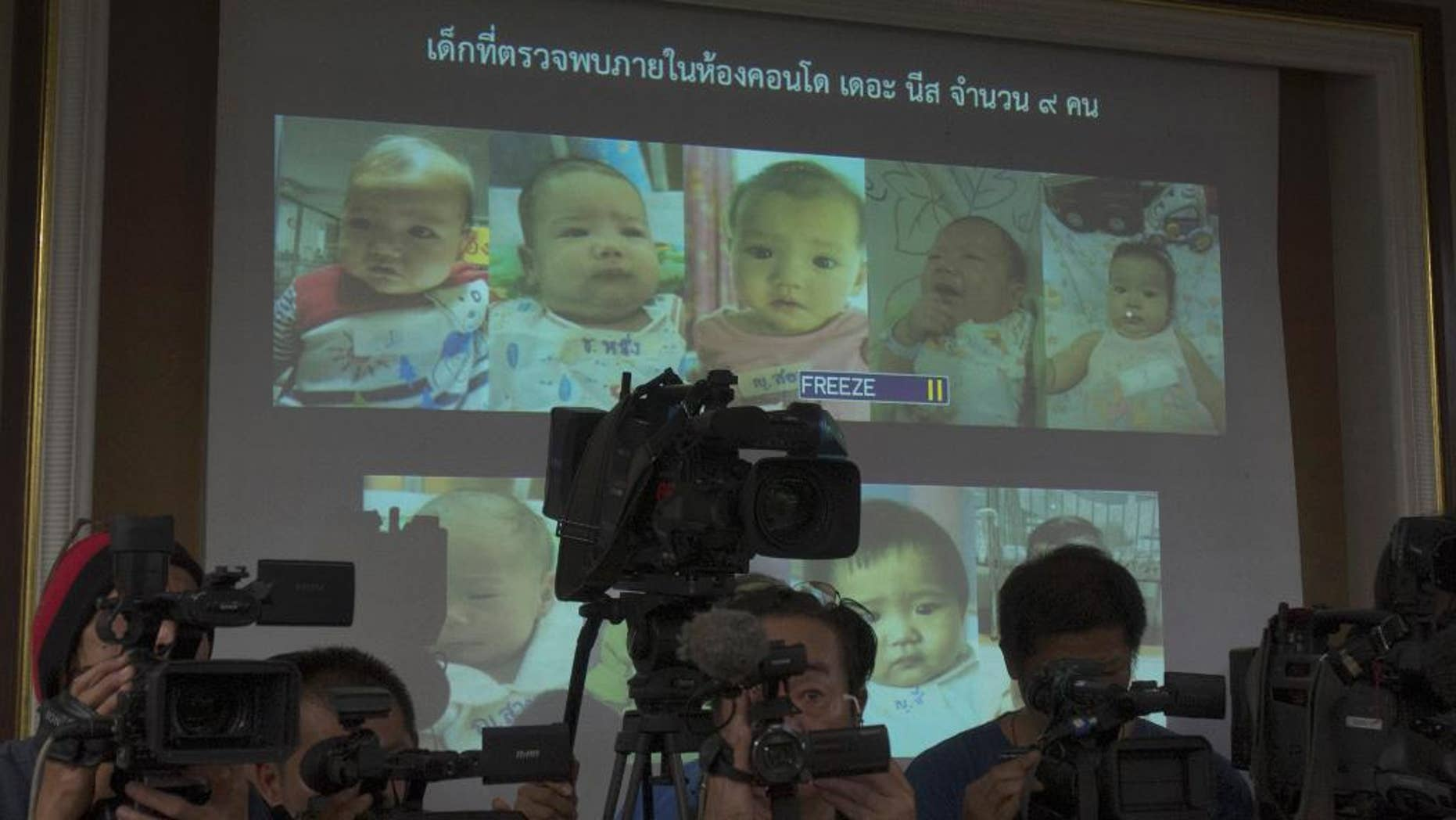 FILE - In this Tuesday, Aug. 12, 2014 file photo, Thai police display pictures of surrogate babies born to a Japanese man who is at the center of a surrogacy scandal during a press conference at the police headquarters in Chonburi, Thailand. A string of recent scandals has lifted a lid on Thailand's largely unregulated commercial surrogacy industry, which has been around for over a decade.  (AP Photo/Sakchai Lalit)