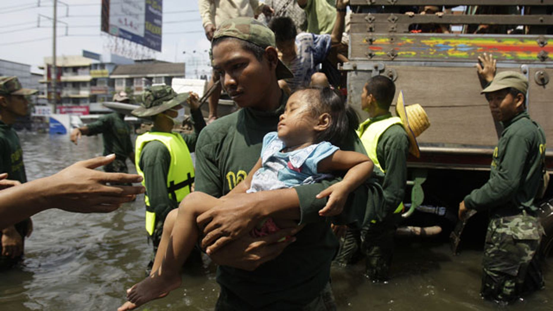 Oct. 21, 2011:  A Thai soldier carries a girl down a truck as they evacuate to higher grounds at the flooded district of Rangsit on the outskirts of Bangkok, Thailand.