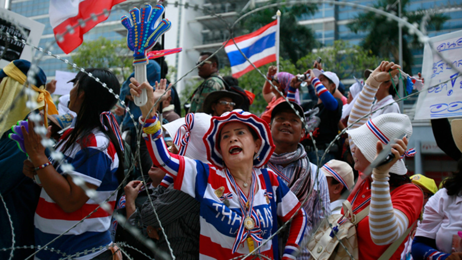 Feb. 19, 2014: Anti-government protesters shout slogans demanding Thai Prime Minister Yingluck Shinawatra to step down during a protest outside her temporary office in the building of the Permanent Secretary of Defense in northern Bangkok, Thailand.