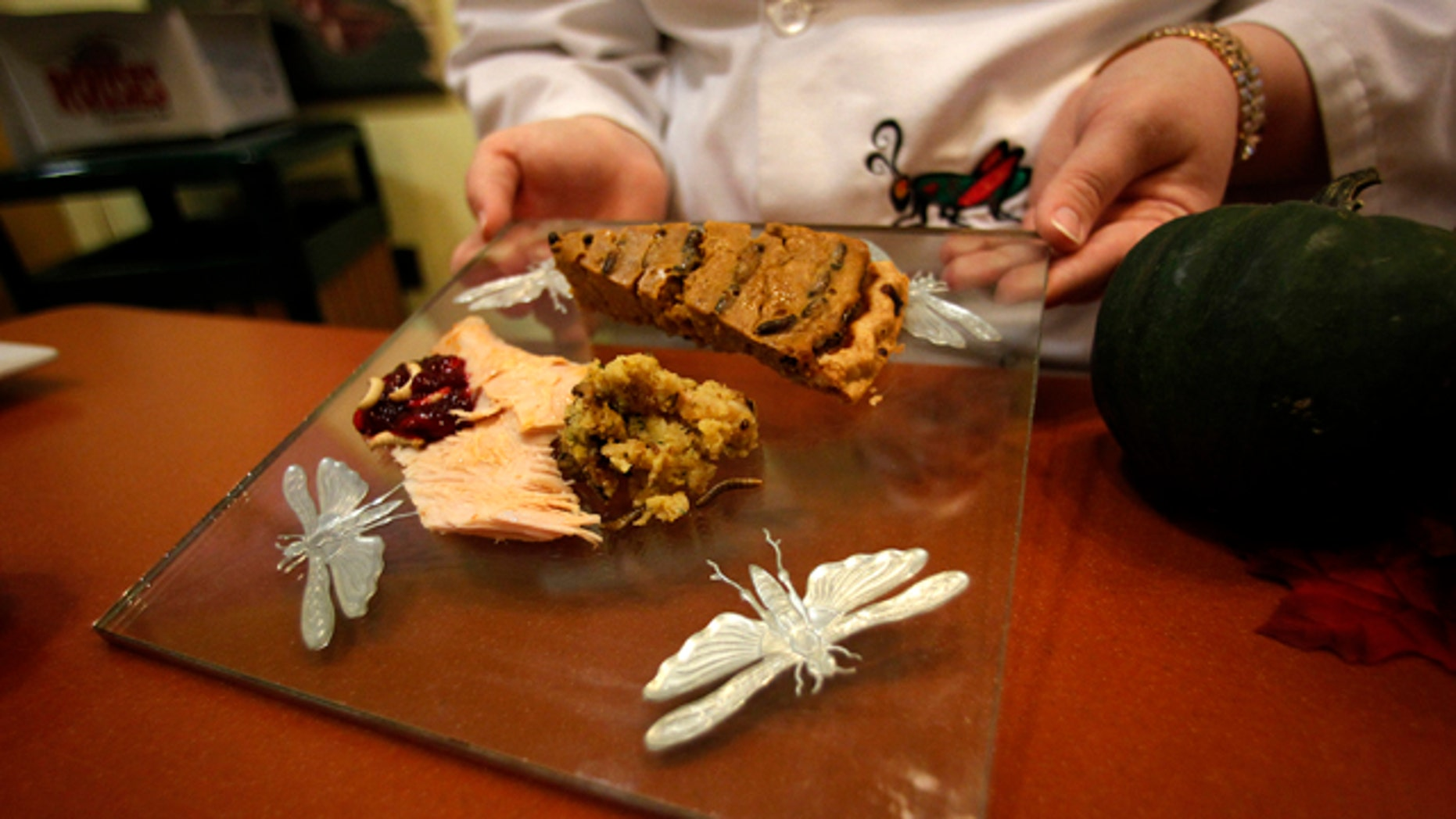 Nov. 11, 2011: Stephanie Smith, an educator at the Audubon Insectarium in New Orleans, shows off a plate of cranberry sauce with wax worms, cricket pumpkin pie, and turkey with cornbread and mealworm stuffing, for visitors to sample Thanksgiving-inspired foods made with insects.