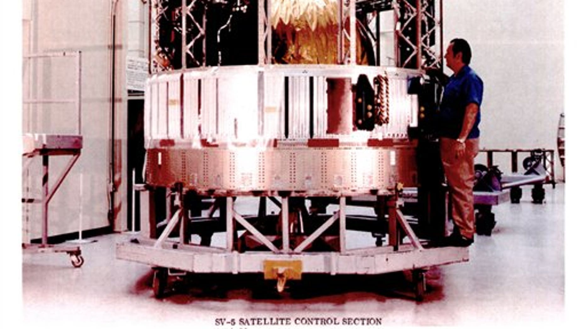 This undated image made available by the National Reconnaissance Office is a declassified image of a man standing next to a satellite control section from the Hexagon program.