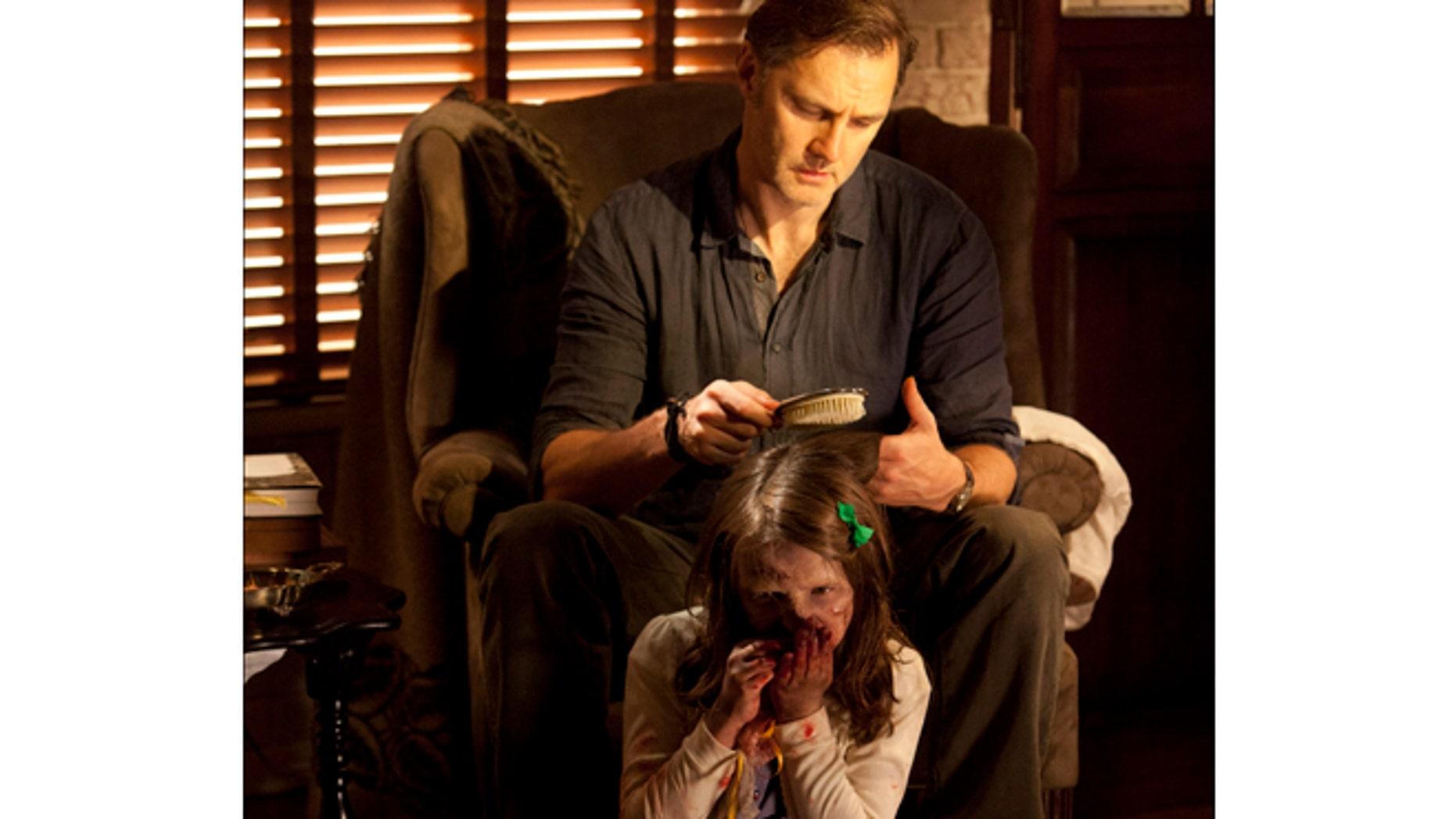 """This undated image released by AMC shows David Morrisey as The Governor brushing the hair of Kylie Szymanski as Penny in a scene from the third season of """"The Walking Dead."""""""