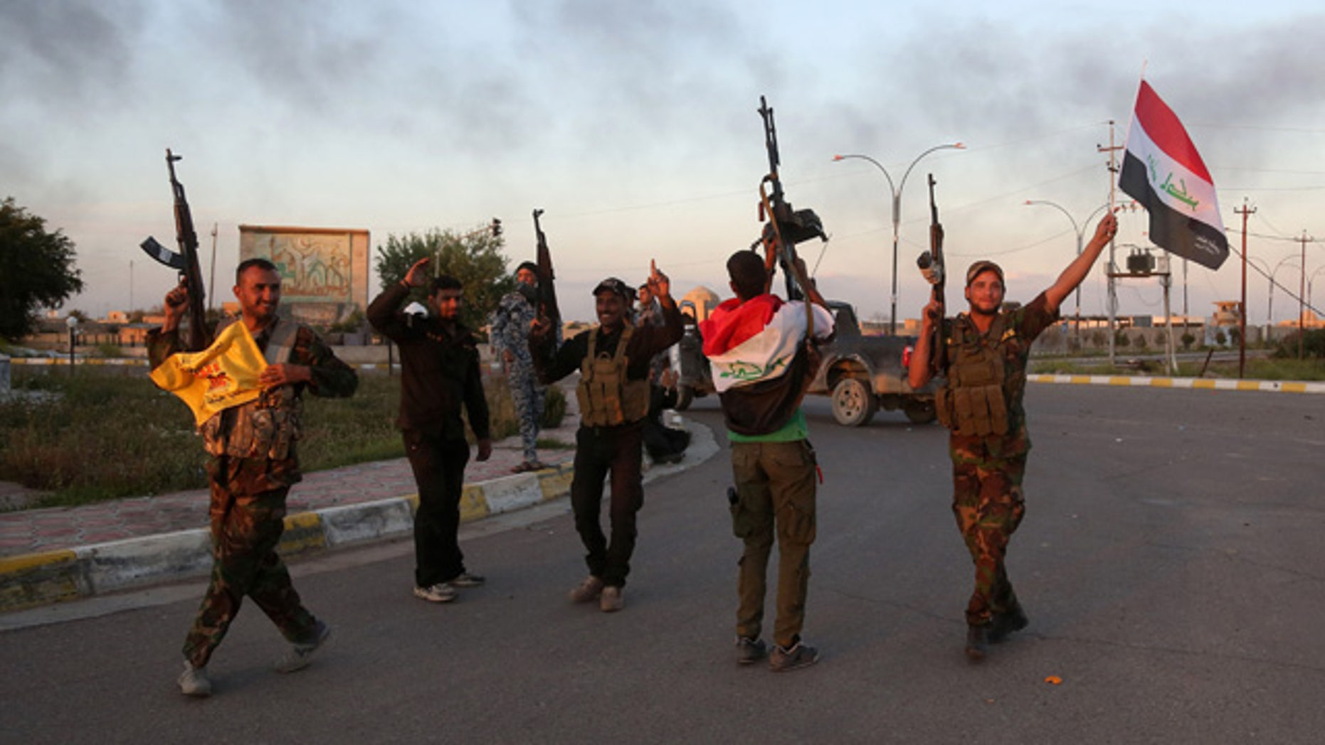 FILE - In this Tuesday, March 31, 2015 file photo, Iraqi security forces and allied Shiite militiamen celebrate in central Tikrit, 80 miles north of Baghdad. (AP Photo/Khalid Mohammed, File)