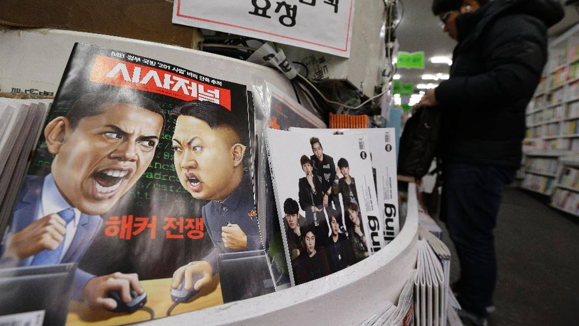 """In this Saturday, Jan. 3, 2015 photo, a magazine with caricatures of U.S. President Barack Obama, left, and North Korean leader Kim Jong Un is displayed at a book store in Seoul, South Korea. The United States imposed new sanctions Friday on North Korean government officials and the country's defense industry for a cyberattack against Sony, insisting that Pyongyang was to blame despite lingering doubts by the cyber community. The red letters on the magazine read """" Hacker War."""" (AP Photo/Ahn Young-joon)"""