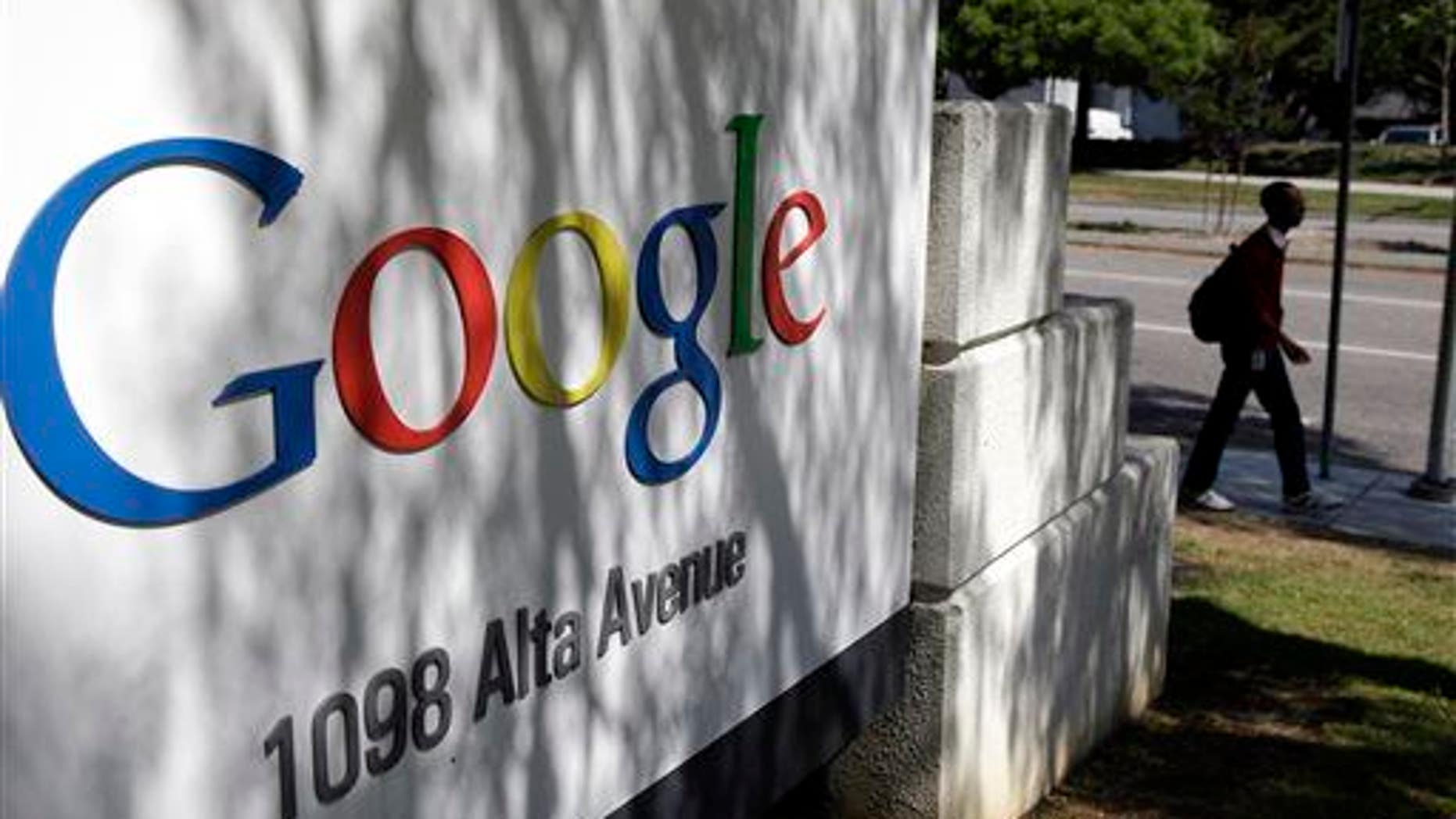 In this June 5, 2014, photo, a man walks past a Google sign at the company's headquarters in Mountain View, Calif.