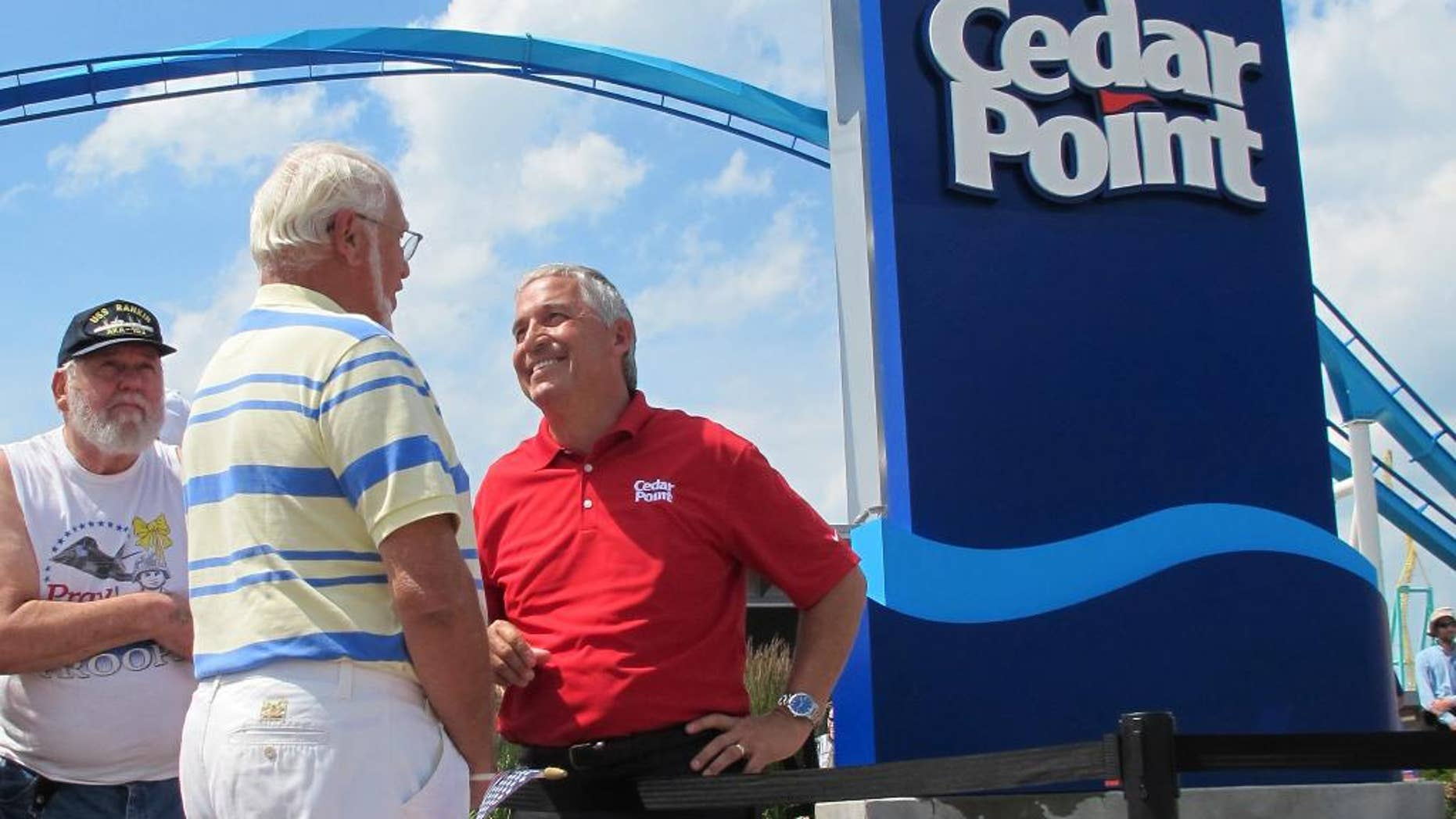 FILE - In this July 2, 2014, file photo, Matt Ouimet, chief executive of Cedar Fair Entertainment Co., greets a guest at Cedar Point amusement park, in Sandusky, Ohio. A man who entered a restricted area at the amusement park to look for a lost cellphone has been struck by a roller coaster and killed Thursday, Aug. 13, 2015. (AP Photo/John Seewer, File)