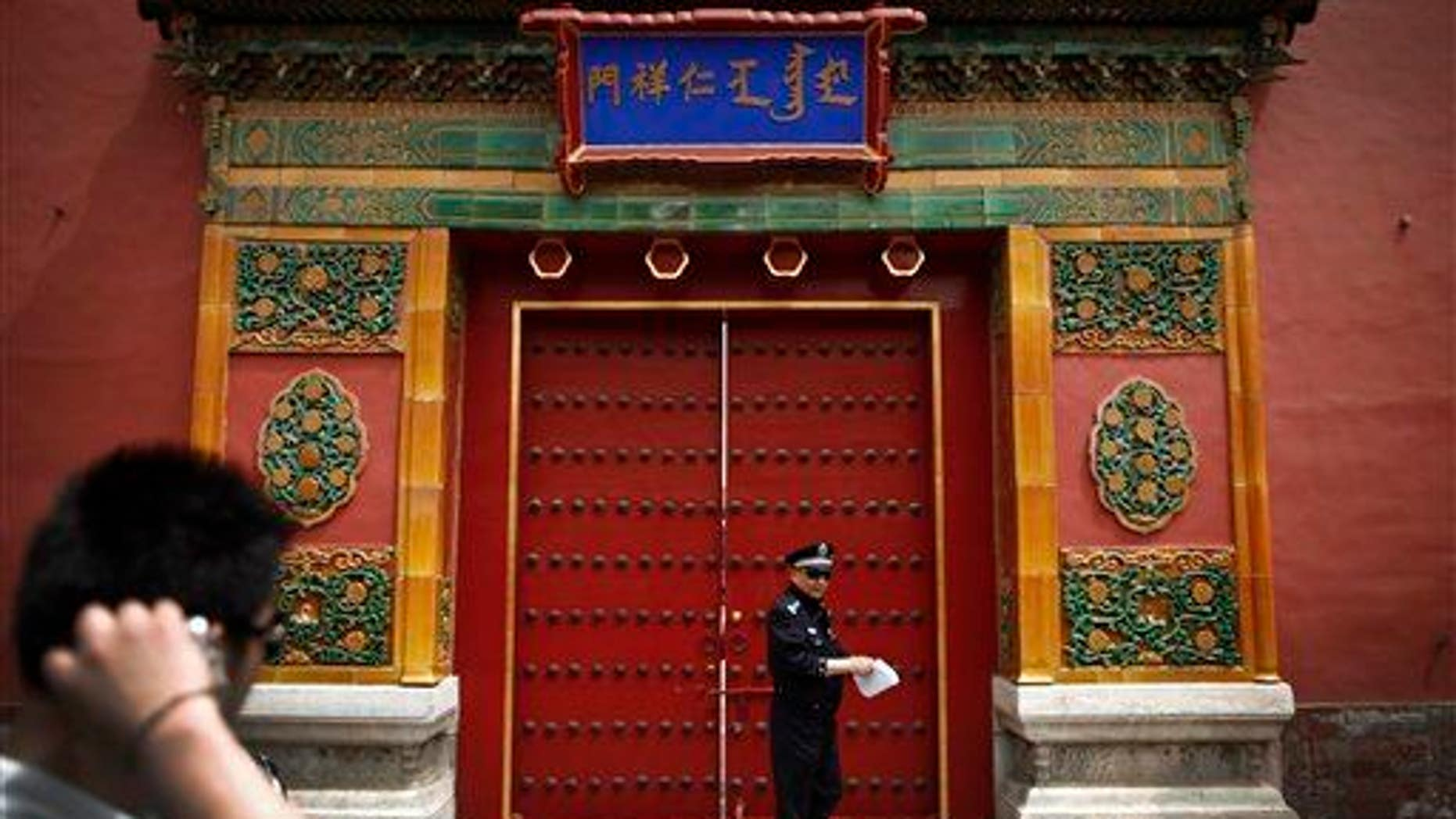 A tourist looks at a policeman stand in front of the entrance doorway to the Palace Museum, which announced the find.