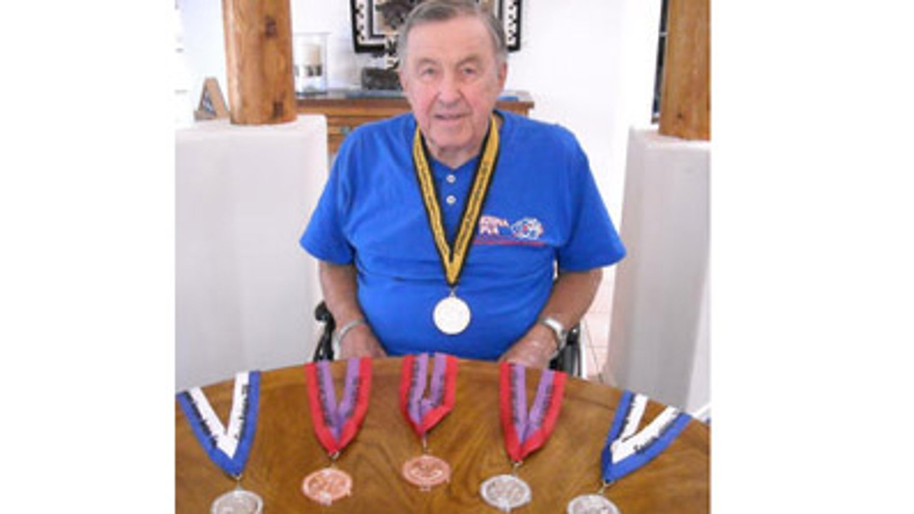 In this Sept. 16, 2011 photo, Theron Hallock sits with his medals in his Green Valley, Ariz., home. Hallock hasnt walked in 10 years but that hasnt stopped him from becoming a national-level athlete. Hallock, who turns 84 soon, recently returned from the 31st Annual National Veterans Wheelchair Games in Pittsburgh, where he took a bronze medal for the power chair relay race.