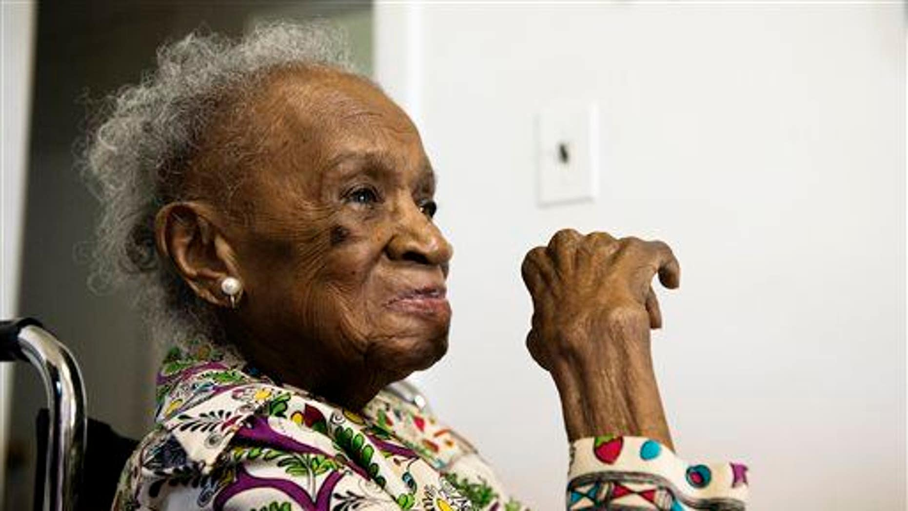 """In this July 16, 2015, photo, Agnes Fenton looks on at her home in Englewood, NJ. Fenton turns 110 on Aug. 1.""""God and Johnnie Walker Blue are the keys to longevity,"""" said Fenton."""