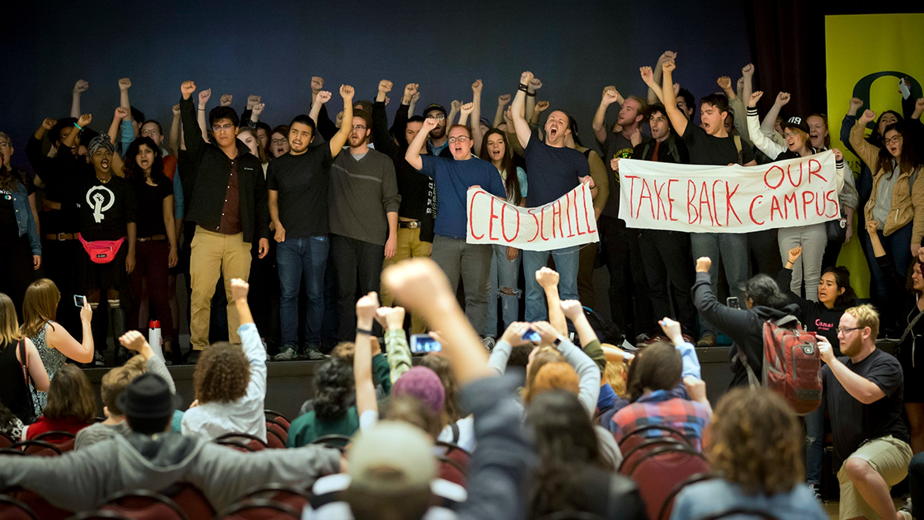 """University of Oregon students chant """"This is a revolution!"""" as they stand on the stage of the Erb Memorial Union Ballroom where President Michael Schill was scheduled to give his State of the University speech in Eugene, Ore., Friday October 6, 2017."""