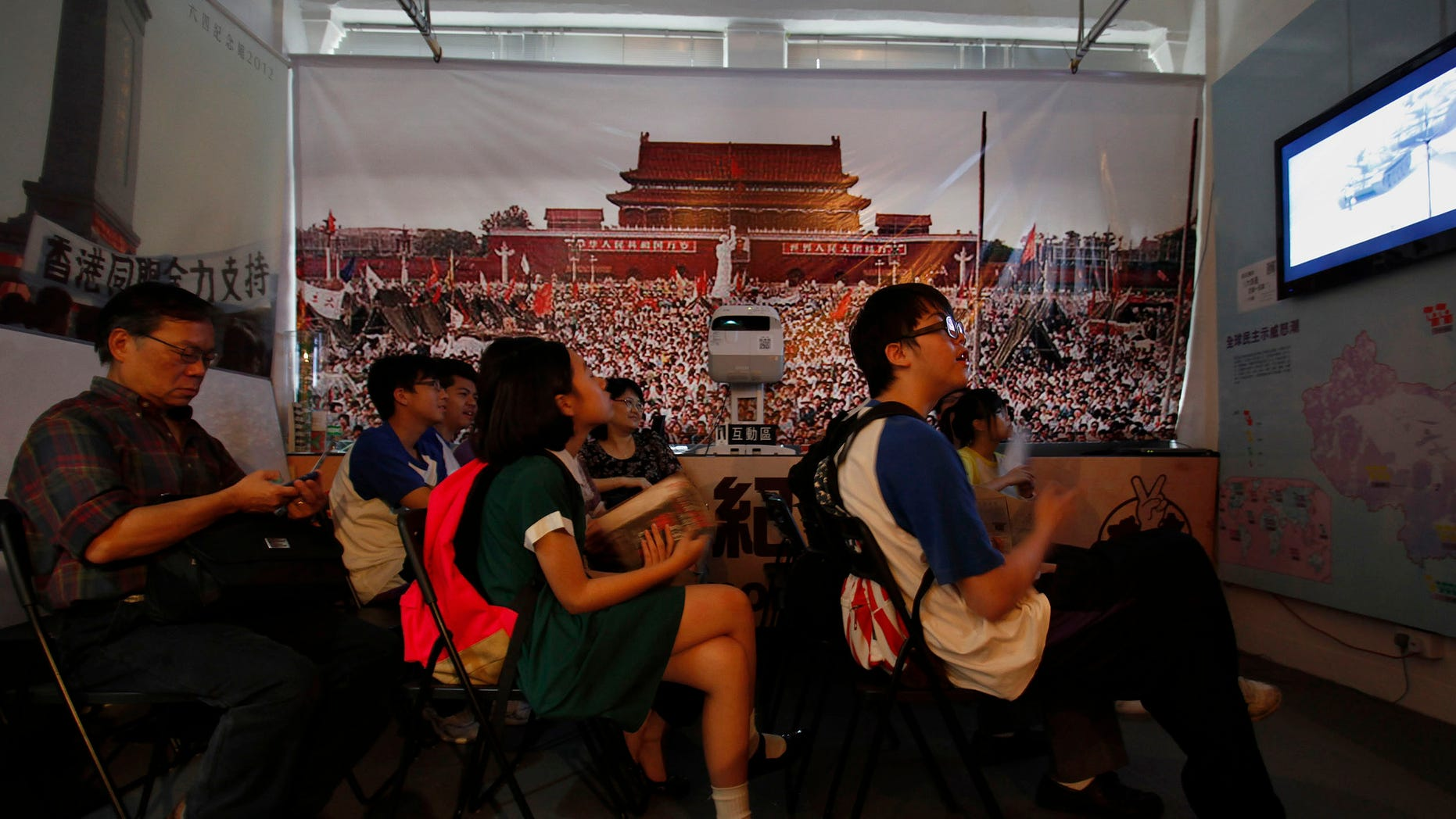 May 31, 2012: Students watch video footage of the crackdown of the 1989 pro-democracy movement at Beijing's Tiananmen Square, inside a residential block run by activists that serves as a temporary museum for displaying items relating to the event, in Hong Kong.
