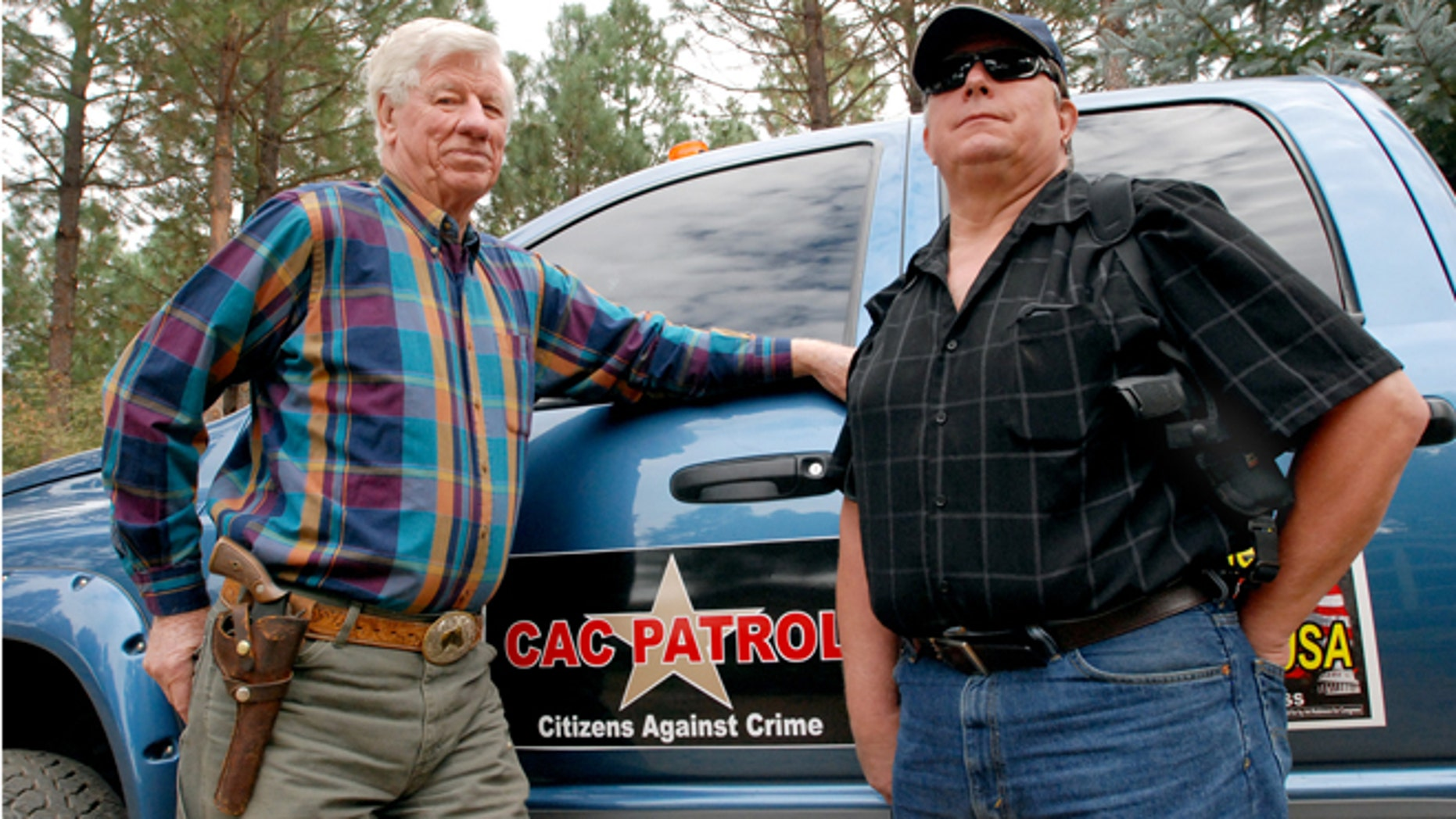 Oct. 12: Sam Nichols, left, and Glenn Woodbury pose in front of Woodbury's pickup in O'Brien, Ore. The two men are part of a neighborhood watch that does armed patrols around the rural area to deter crime since budget cutbacks have left the Josephine County Sheriff's Office with just three patrol deputies and limited jail space.