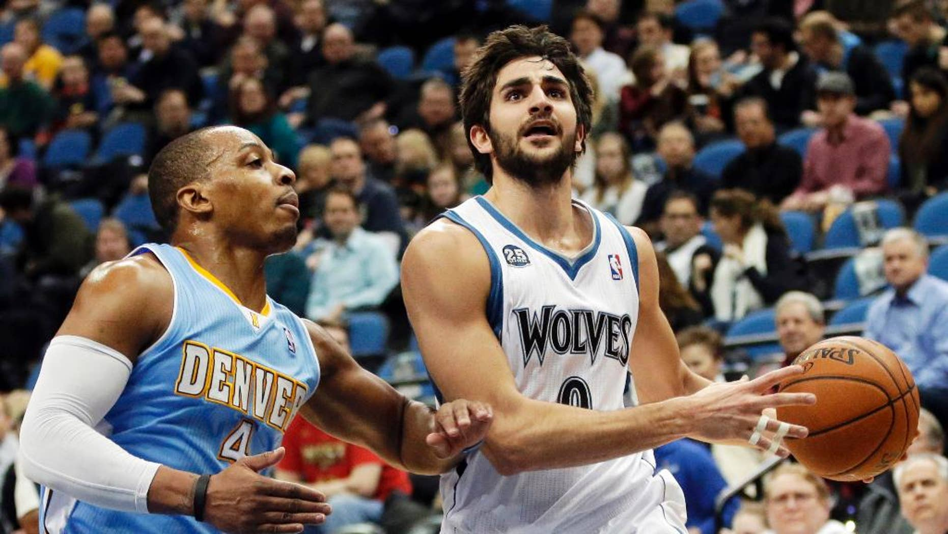 FILE - In this Feb. 12, 2014, file photo, Minnesota Timberwolves' Ricky Rubio, right, of Spain, lays up a shot as Denver Nuggets's Randy Foye defends in the first quarter of an NBA basketball game in Minneapolis. The clock is ticking on the  Timberwolves and Rubio to get an extension done. If the two sides don't reach agreement by Oct. 31, Rubio can become a restricted free agent next summer. (AP Photo/Jim Mone, File)