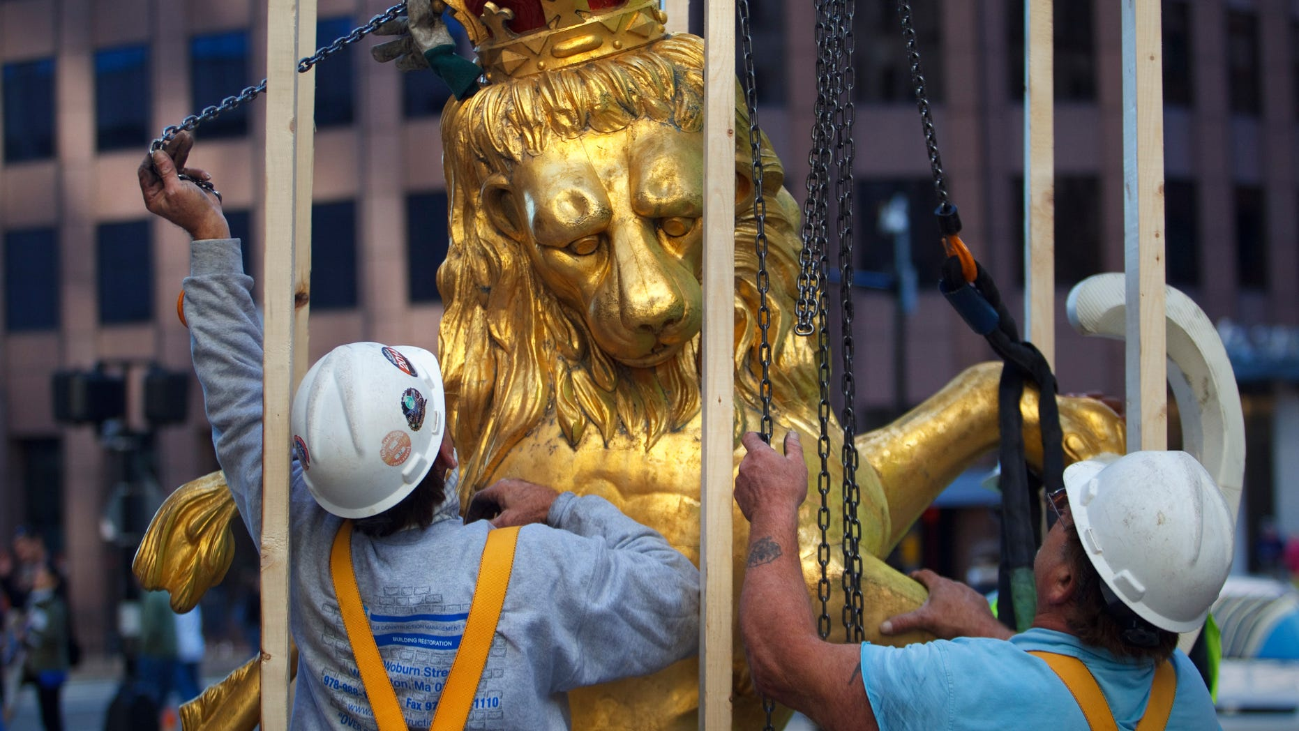 Sept. 14, 2014: A lion statue is removed from atop the Old State House on Washington Street in Boston. (AP/The Boston Globe, Dina Rudick)