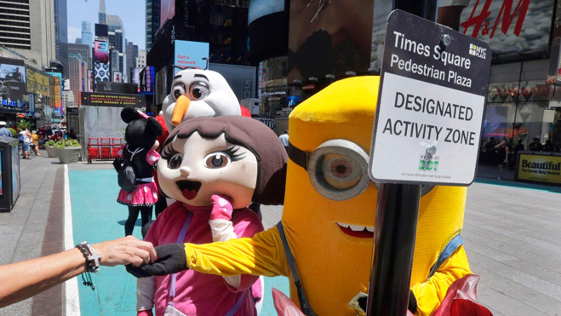 Costumed characters work in New York's Times Square, Tuesday, June 21, 2016.
