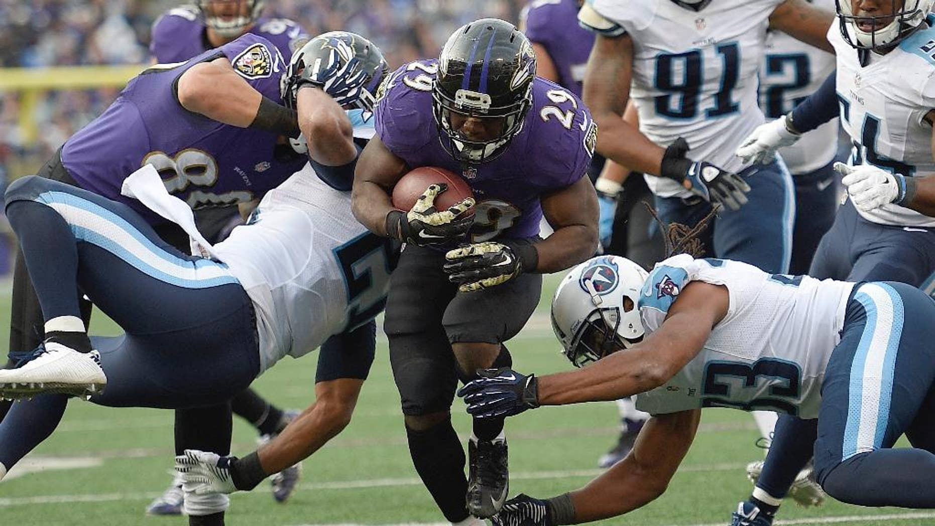 Baltimore Ravens running back Justin Forsett (29) slips past Tennessee Titans free safety Michael Griffin (33) and runs for a touchdown during the second half of an NFL football game in Baltimore, Sunday, Nov. 9, 2014. (AP Photo/Nick Wass)