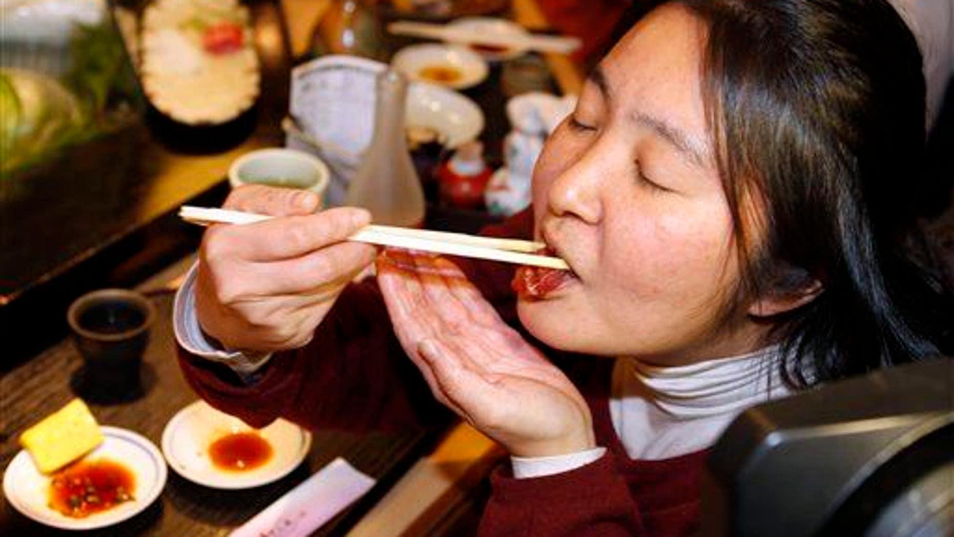 A woman eats a sushi of a bluefin tuna in Tokyo.