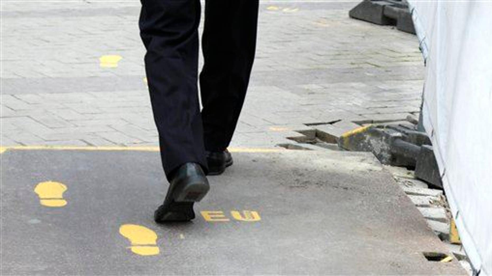 A man follows a yellow foot path in Brussels, Wednesday, June 27, 2012.