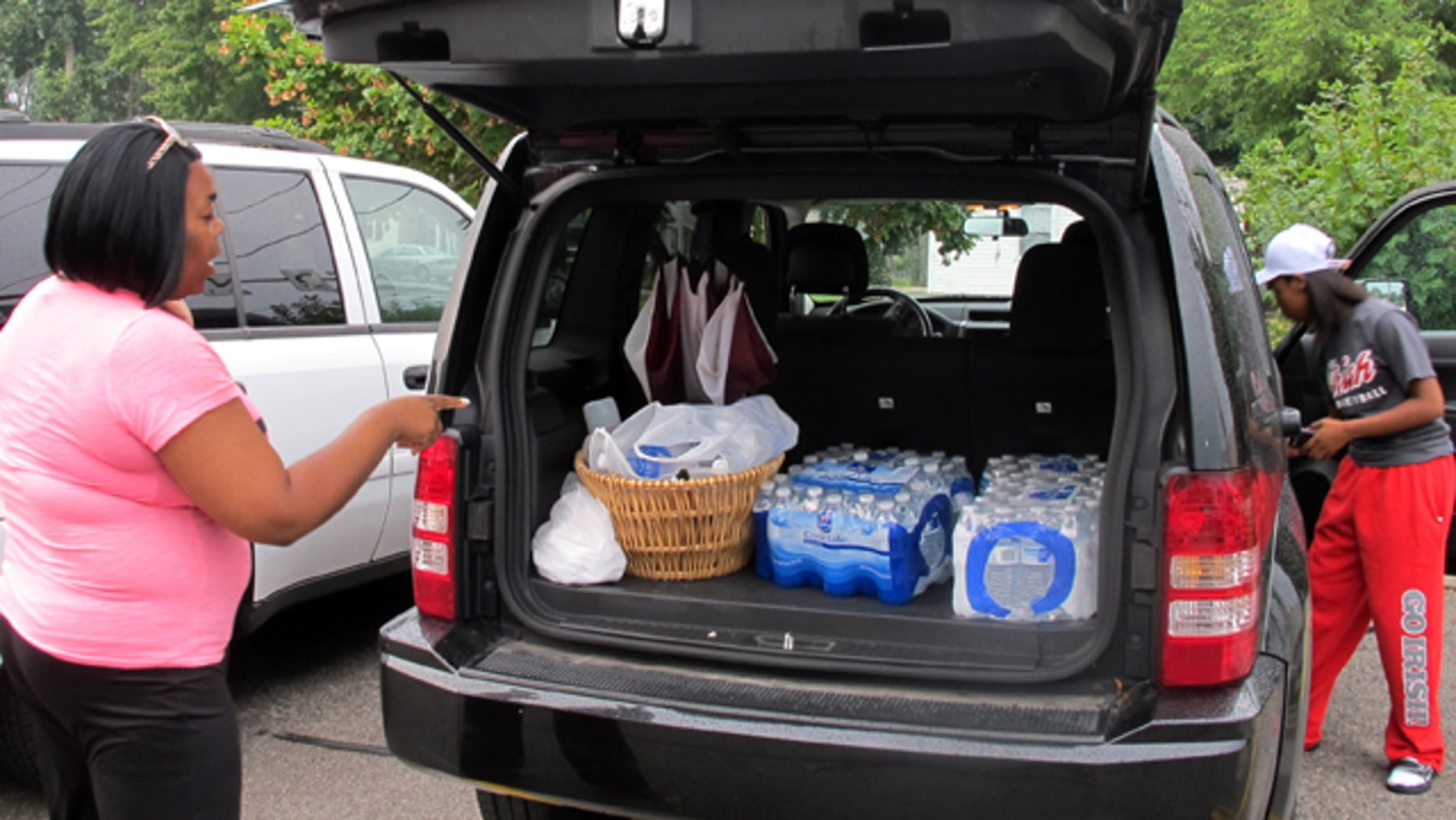 August 2, 2014: Aundrea Simmons stands next to her minivan with cases of bottled water she bought after Toledo warned residents not to use its water. About 400,000 people in and around Ohio's fourth-largest city were warned not to drink or use its water after tests revealed the presence of a toxin possibly from algae on Lake Erie. (AP Photo/John Seewer)