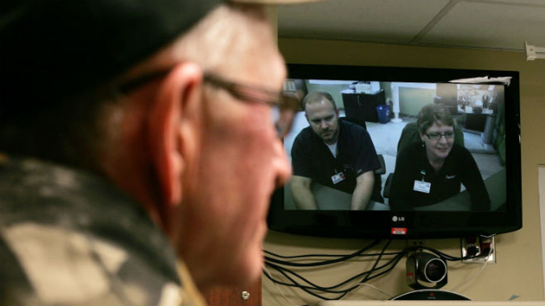 South Dakota rancher Tom Soukup looks at a video monitor at a hospital in Wagner, S.D., that connects its clinic with Avera Health physicians in Sioux Falls, SD. (AP photo/Jeremy Waltner)