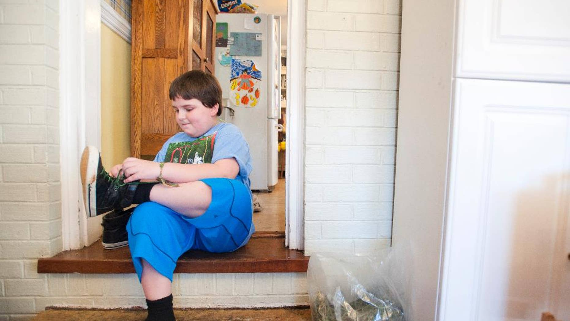 Sunnie Kahle, 8, puts on her shoes before leaving her home in Forest, Va. on March 26, 2014.  Kahle recently withdrew from Timberlake Christian School in Forest, Va. after the school sent a letter asking her to either dress and act more feminine or not enroll again because she looked too much like a boy. (AP Photo/The News & Advance, Jill Nance)