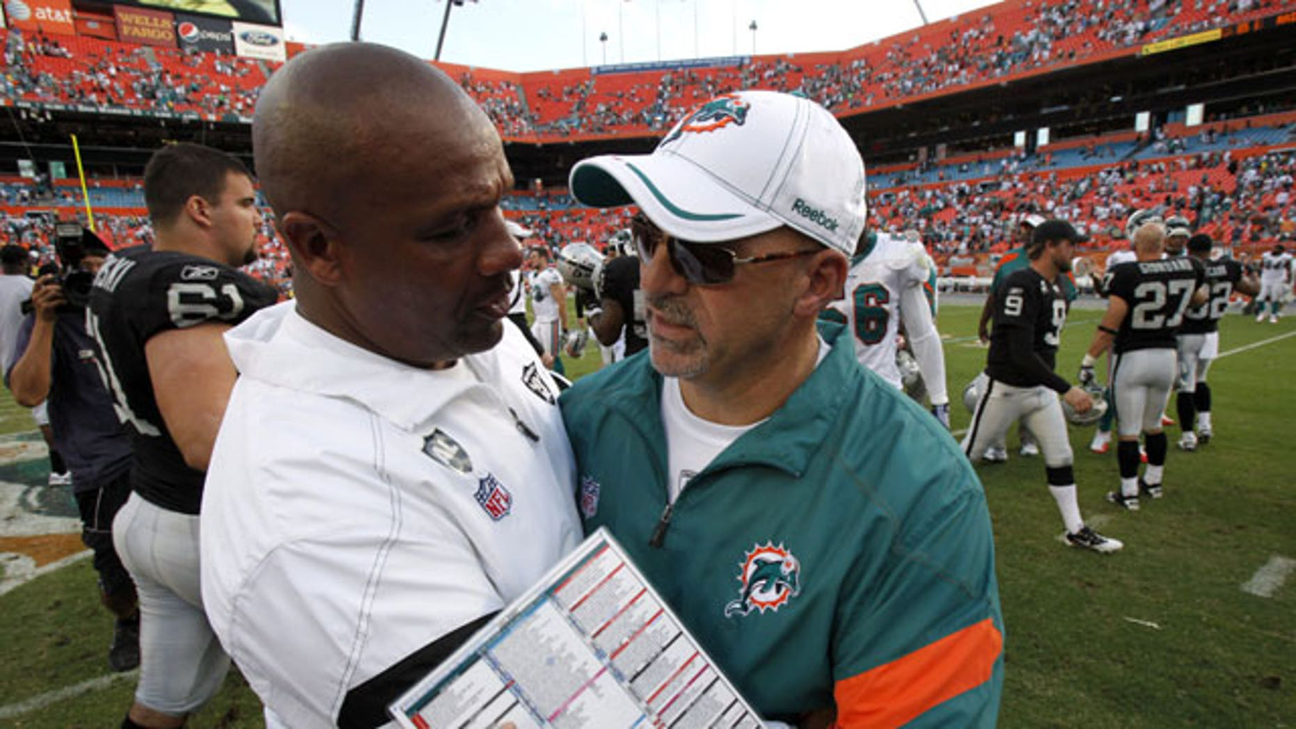 December 4, 2011: Oakland Raiders head coach Hue Jackson, left, and Miami Dolphins head coach Tony Sparano congratulate each other after the Dolphins defeated the Raiders 34-14 in an NFL football in Miami.