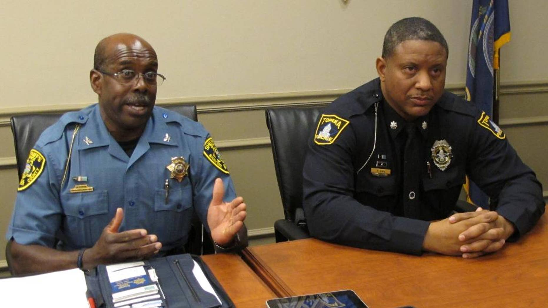 Shawnee County, Kan., Sheriff Herman Jones, left, answers questions from reporters about the shooting death of a Topeka police officer, as interim Police Chief Tony Kirk, right, watches, Sunday, Sept. 7, 2014, in Topeka, Kan. The officer, Cpl. Jason Harwood, 40 was shot during a car stop in east Topeka. (AP Photo/John Hanna)