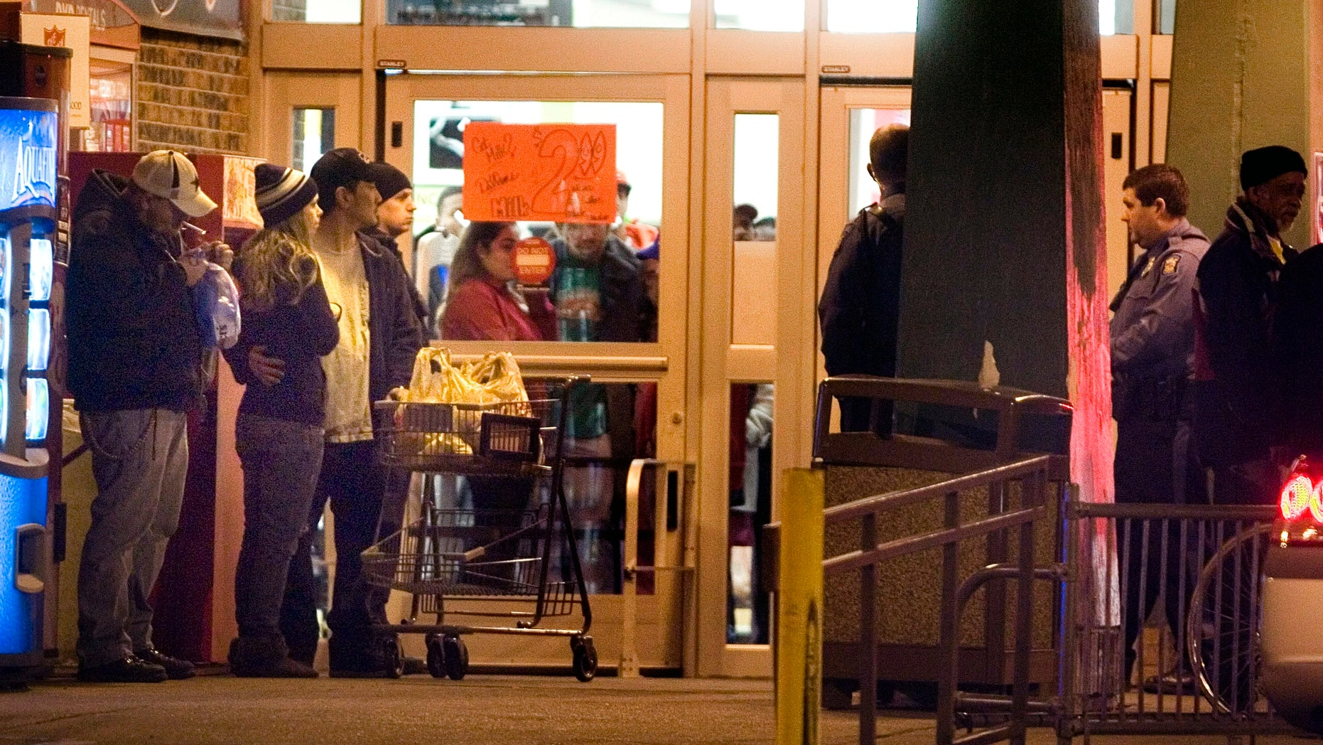 Dec. 16, 2012: Bystanders watch as Topeka police investigate at the scene of a shooting outside a grocery store in Topeka, Kan.