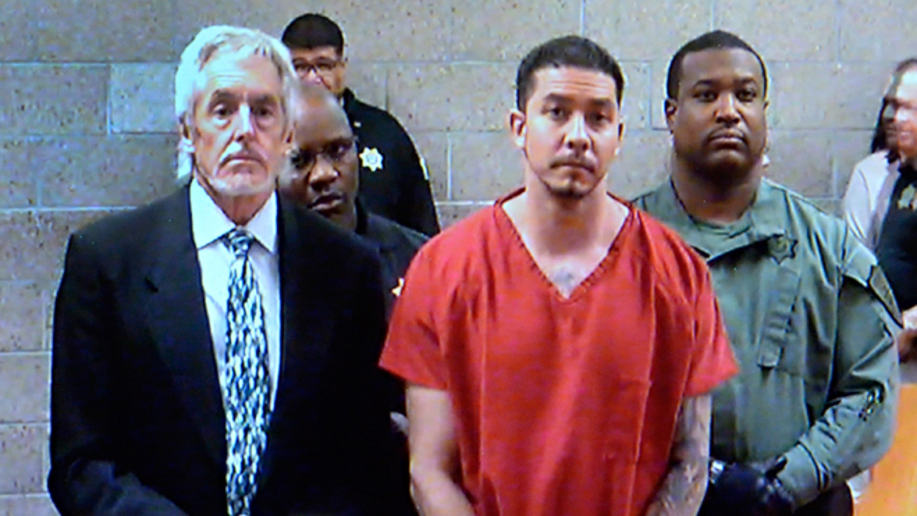In this video frame grab provided by the Albuquerque Metro Court, Tony Torrez, center, stands with public defender Jeff Rein, left, while making an appearance at the Albuquerque Metro Court via video in Albuquerque, N.M., Thursday, Oct. 22, 2015. Torrez has been charged with murder, assault, child abuse and other crimes following his arrest Wednesday in a deadly road rage shooting that killed a 4-year-old girl. (Albuquerque Metro Court/The Albuquerque Journal via AP, Pool)