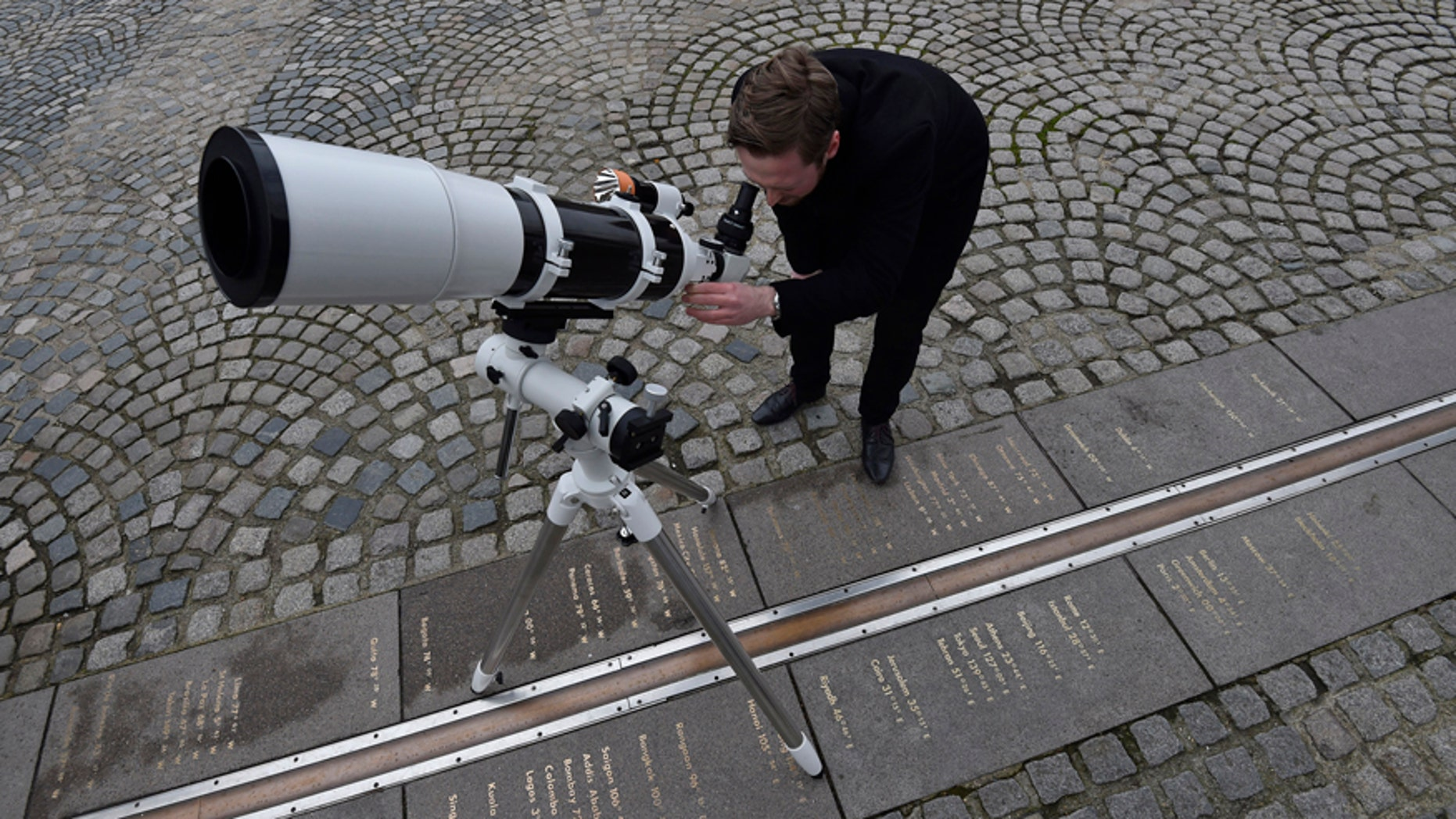 Astronomer Brendan Owens poses with a refractive telescope on the Meridian line at The Royal Observatory in Greenwich, south east London March 19, 2015.
