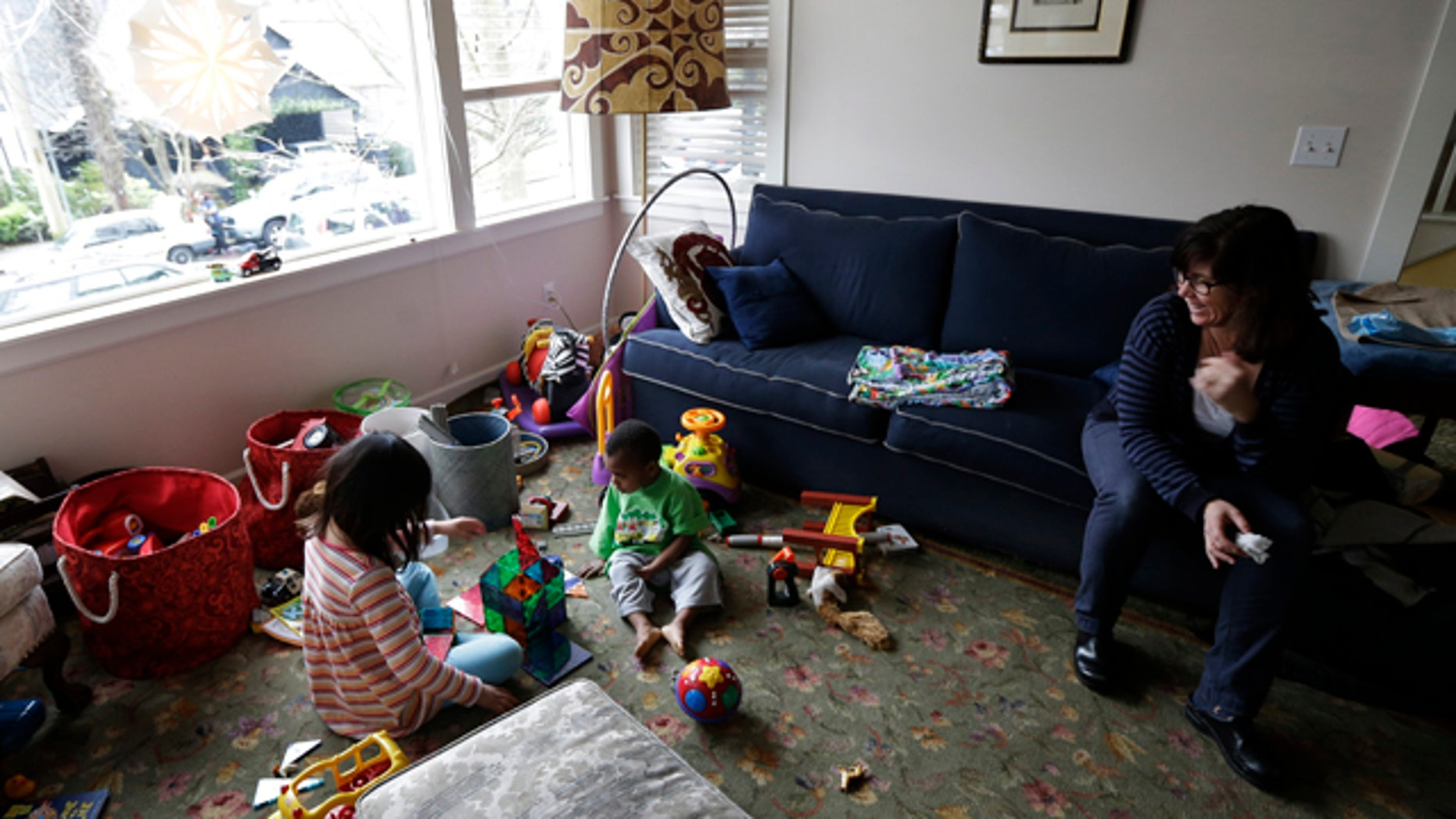 Feb. 12, 2013: Nancy Jensen, right, watches as her children, Elizabeth, 6, left, and Joe, 2, center, play with a building set and other toys.