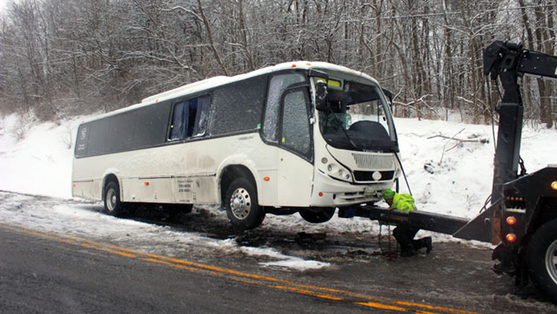 February 9, 2014: An Interstate Emergency Services employee hooks up a bus to a tow truck to pull it out of the ditch on Route 220 in Cumberland Valley Twp., Pa. (AP Photo/Bedford Gazette, Bridgett Weaver)