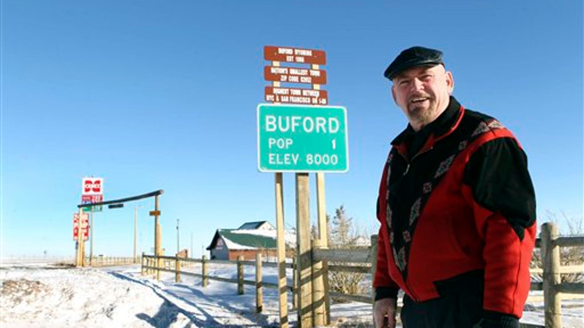 FILE  -  This Jan. 1, 2011 file photo shows Buford resident Don Sammons standing in front of the population sign in Buford, Wyo.
