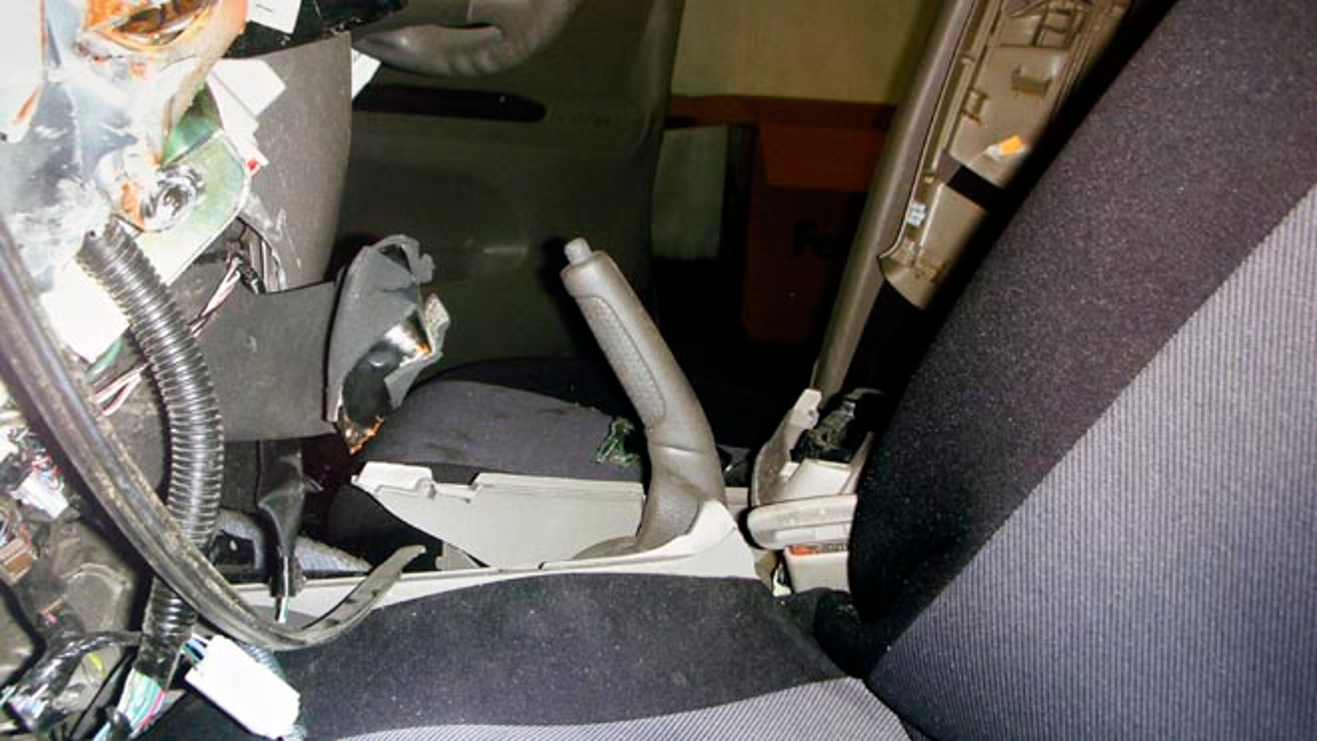"""FILE - In this undated file photo displayed during a news conference by the family of the Noriko Uno, who died in an alleged """"sudden unintended acceleration"""" auto crash in August 2009, a photo of the interior of her Toyota 2006 Camry is shown with the hand brake handle pulled all the way back. Uno's case, in which her family claims her vehicle accelerated suddenly despite her efforts, is the first headed to trial where the Japanese automaker is accused of covering up defects that led to her death. (AP Photo/Uno Family, File)"""
