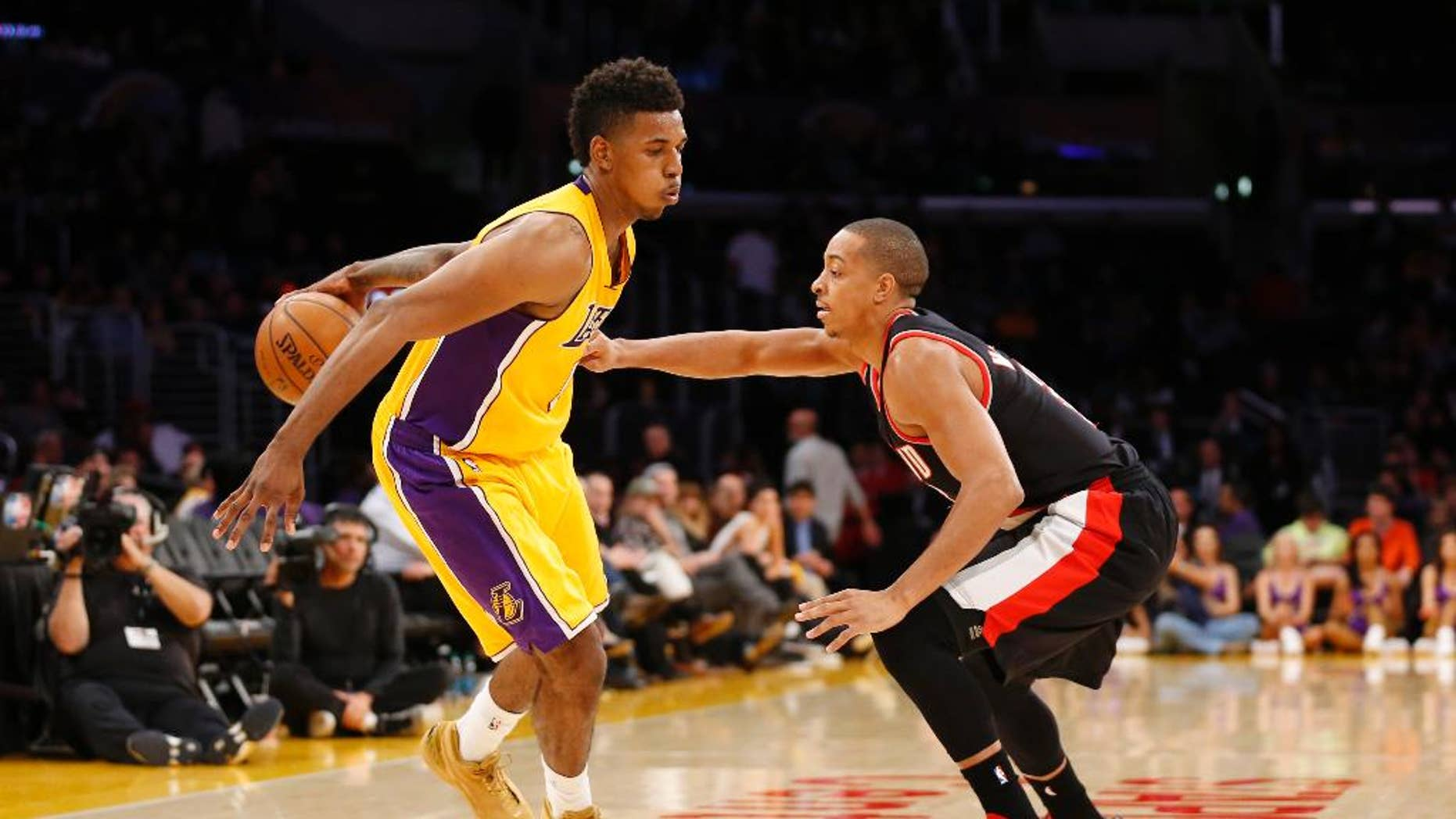 Los Angeles Lakers forward Nick Young dribbles behind his back as Portland Trail Blazers guard C.J. McCollum defends during the second half of an NBA basketball game in Los Angeles, Tuesday, April 1, 2014. The Trail Blazers won 124-112. (AP Photo/Danny Moloshok)