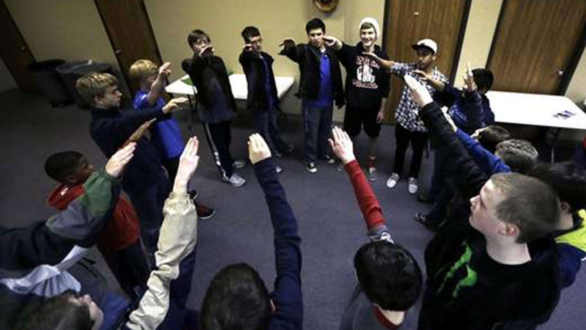 """Trail Life members move their arms as they and sing """"Taps"""" in a circle during a meeting in North Richland Hills, Texas. Trail Life USA, the new Christian-based alternative to the Boy Scouts of America, excludes openly gay members."""