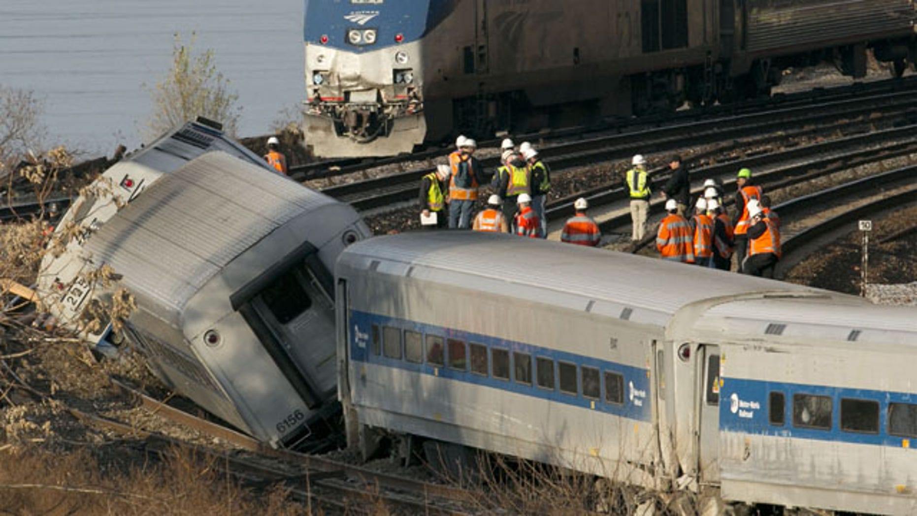 FILE - In this Dec. 1, 2013 file photo, an Amtrak train, top, traveling on an unaffected track, passes a derailed Metro North commuter train in the Bronx borough of New York. (AP Photo)